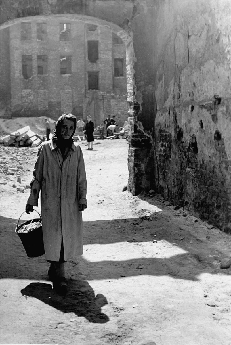 A Jewish woman carries a pail along a street in the Warsaw ghetto.