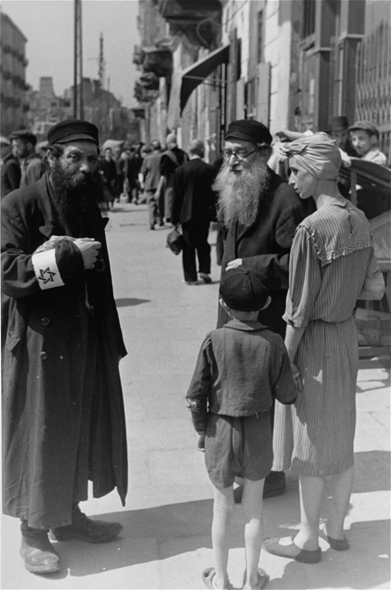 Jews converse on a street in the Warsaw ghetto.