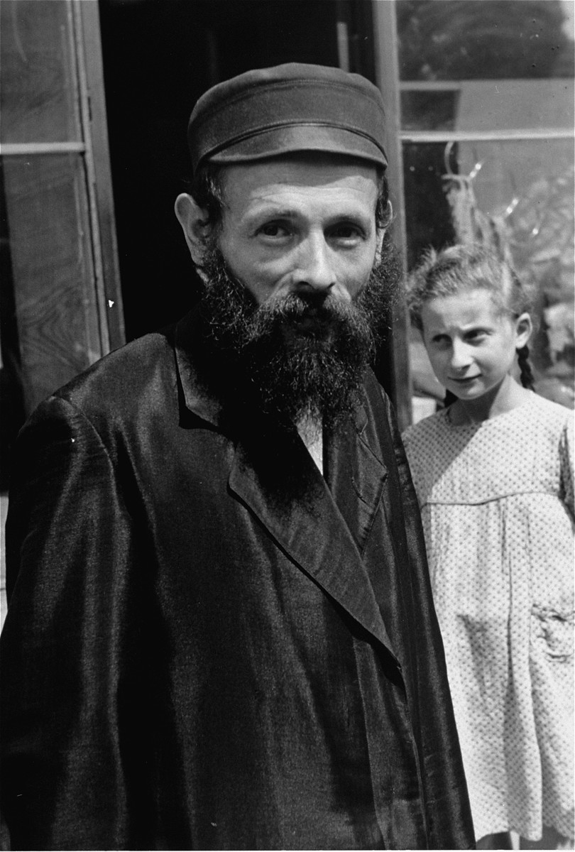 Portrait of a religious Jewish man in the Warsaw ghetto.  A young girl stands behind him.