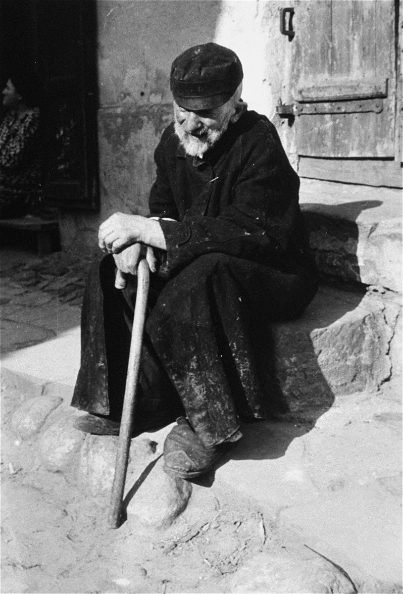 An elderly Jewish man sits on a step outside a door in an unidentified ghetto.