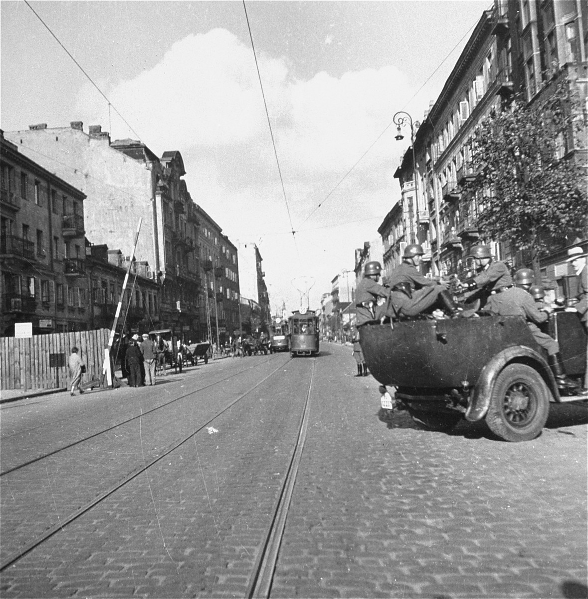 "German police relax in a vehicle at the gate to the Warsaw ghetto on Leszno Street.    Joest's original caption reads: ""At that time, Polish streetcars still traveled at high speed through the ghetto.  This police vehicle just drove through the gate here on Leszno Street.  I asked myself if the man on the running-board is a Polish informer."""