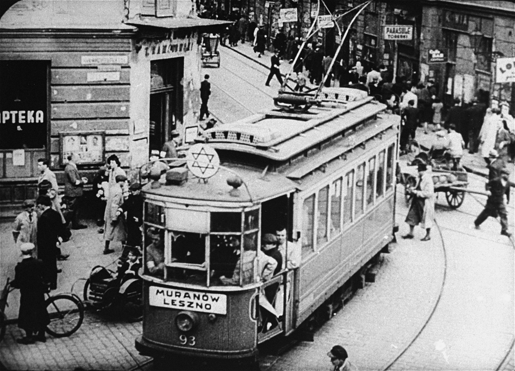 A streetcar turns through the intersection of Leszno and Karmelicka Streets in the Warsaw ghetto.