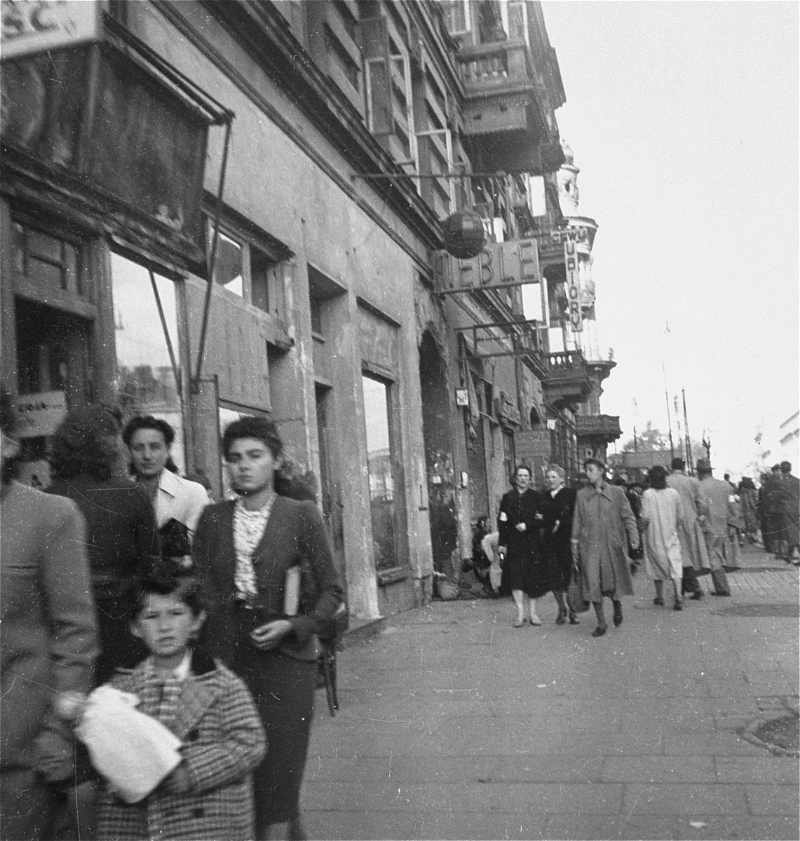 "Jews on the street in the Warsaw ghetto.    Joest's caption reads: ""When I see my own photos again after so many years, I ask myself which of these people survived, who at that time I photographed as normal pedestrians on a large street."""