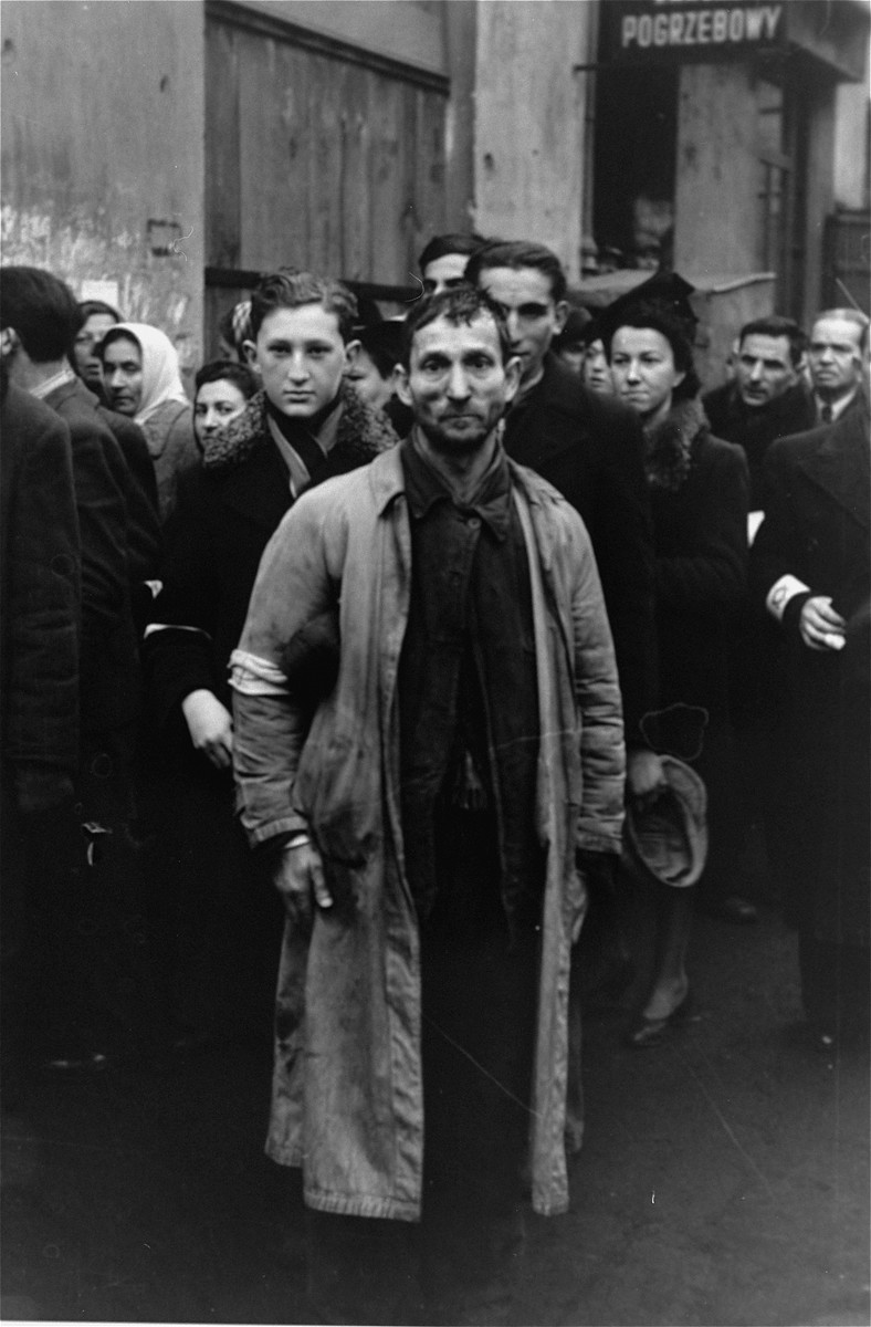 A group of Jews on a street in the Warsaw ghetto doff their hats to the German photographer.  Mietek Grayewski-Grinberg is pictured to the left of the man in the center.