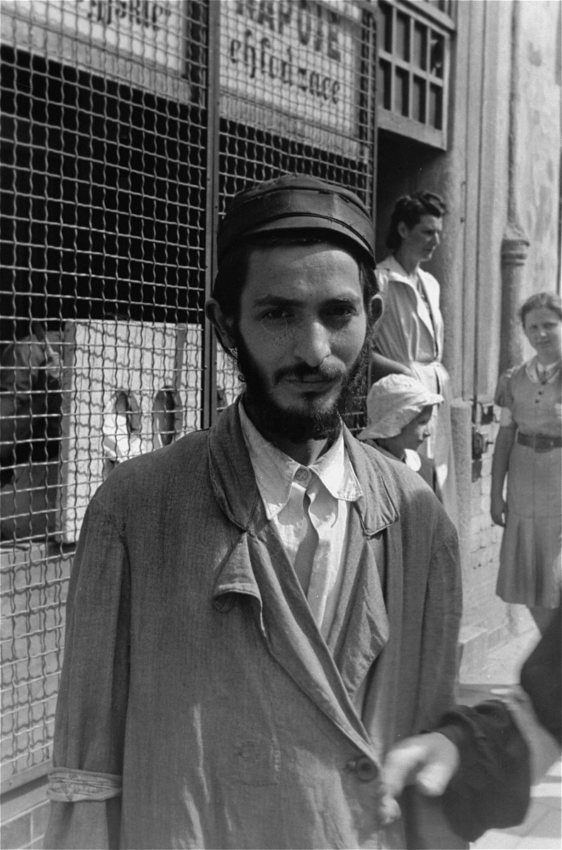 Portrait of a young Jewish man in front of a gated shop in the Warsaw ghetto.