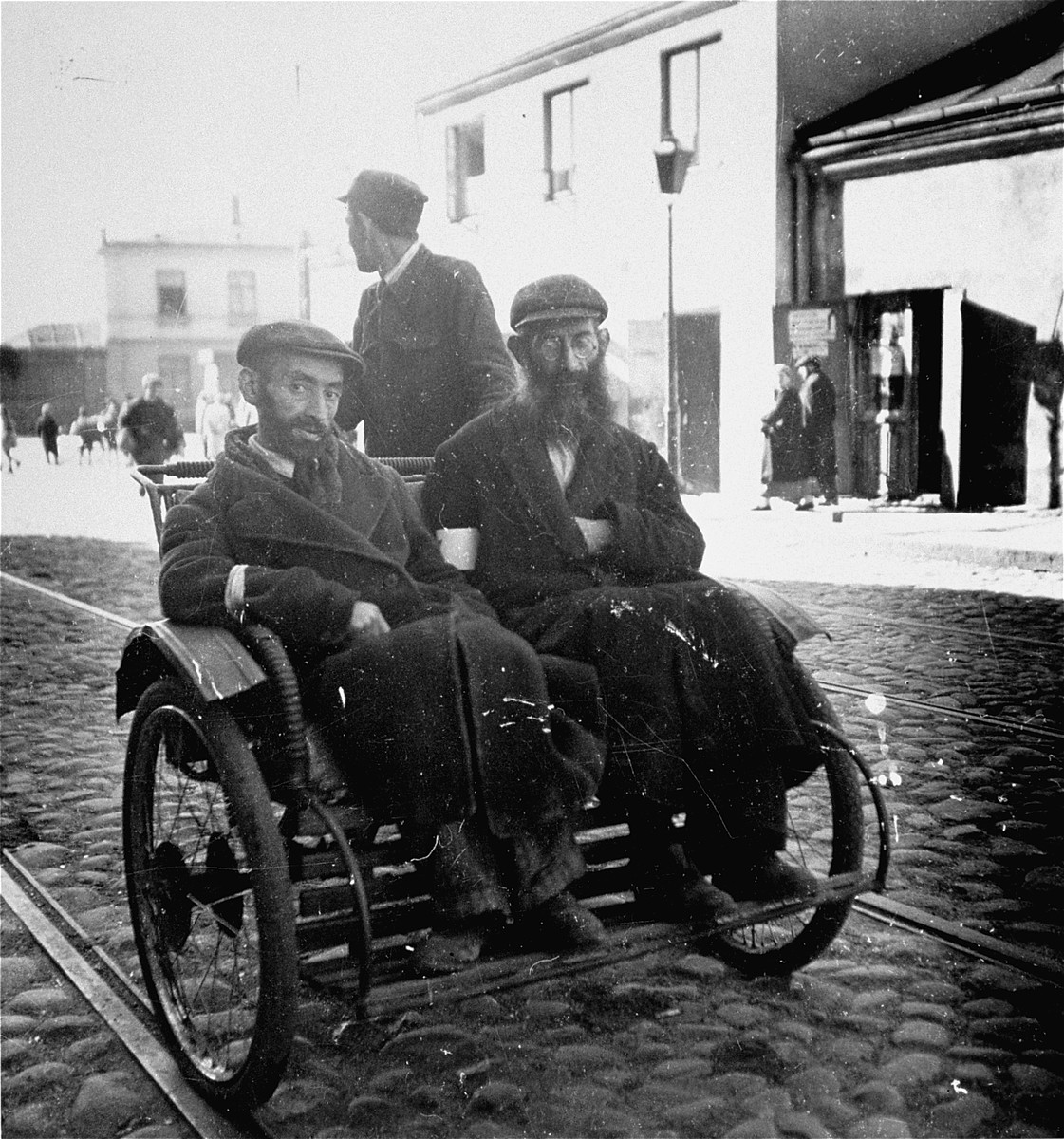 """Two religious Jewish men travel by rickshaw in the Warsaw ghetto.    Joest's caption reads: """"I had earlier never seen human beings used as a means of transportation.  I thought such a thing only existed in India."""""""