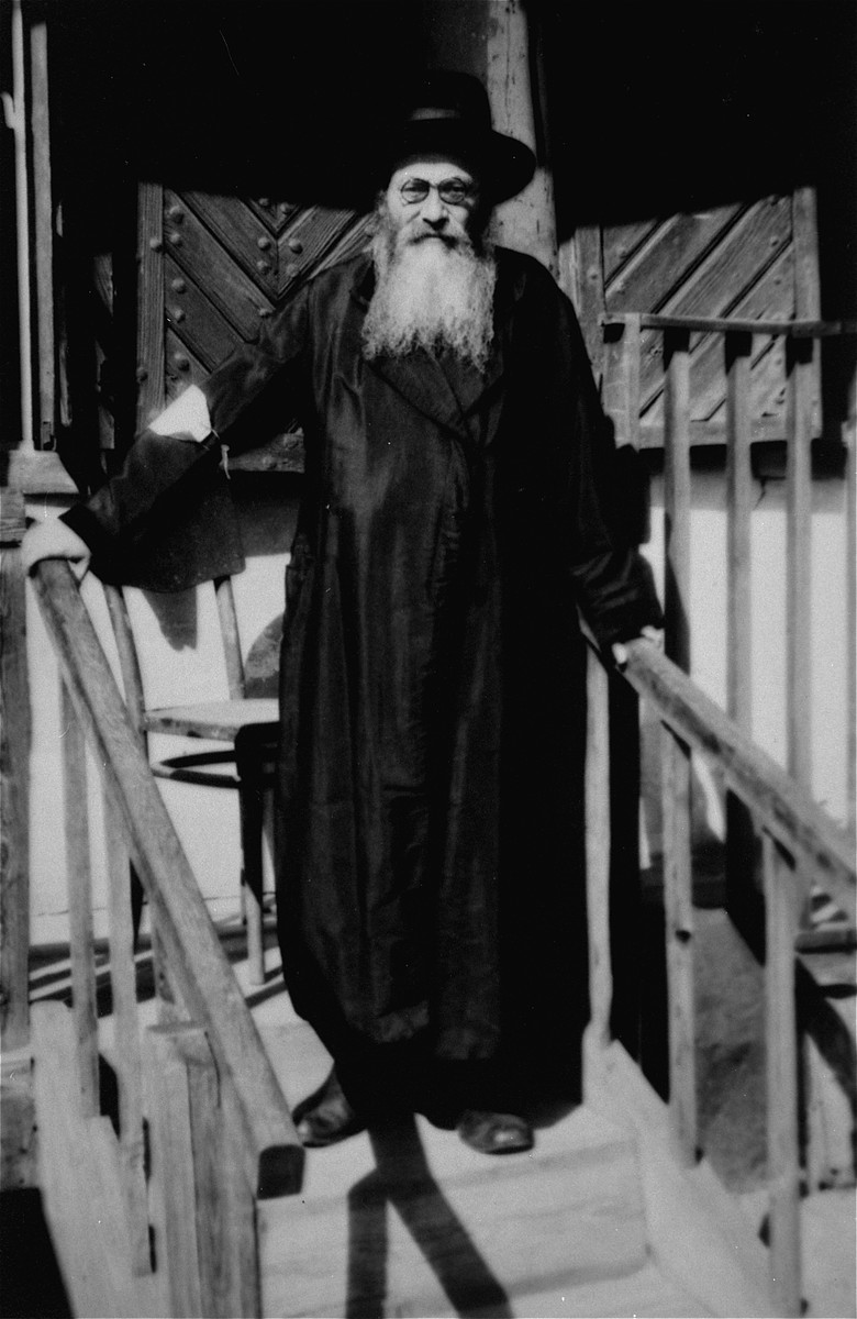 An elderly religious Jew wearing an armband poses on a staircase outside a house in an unidentified ghetto.