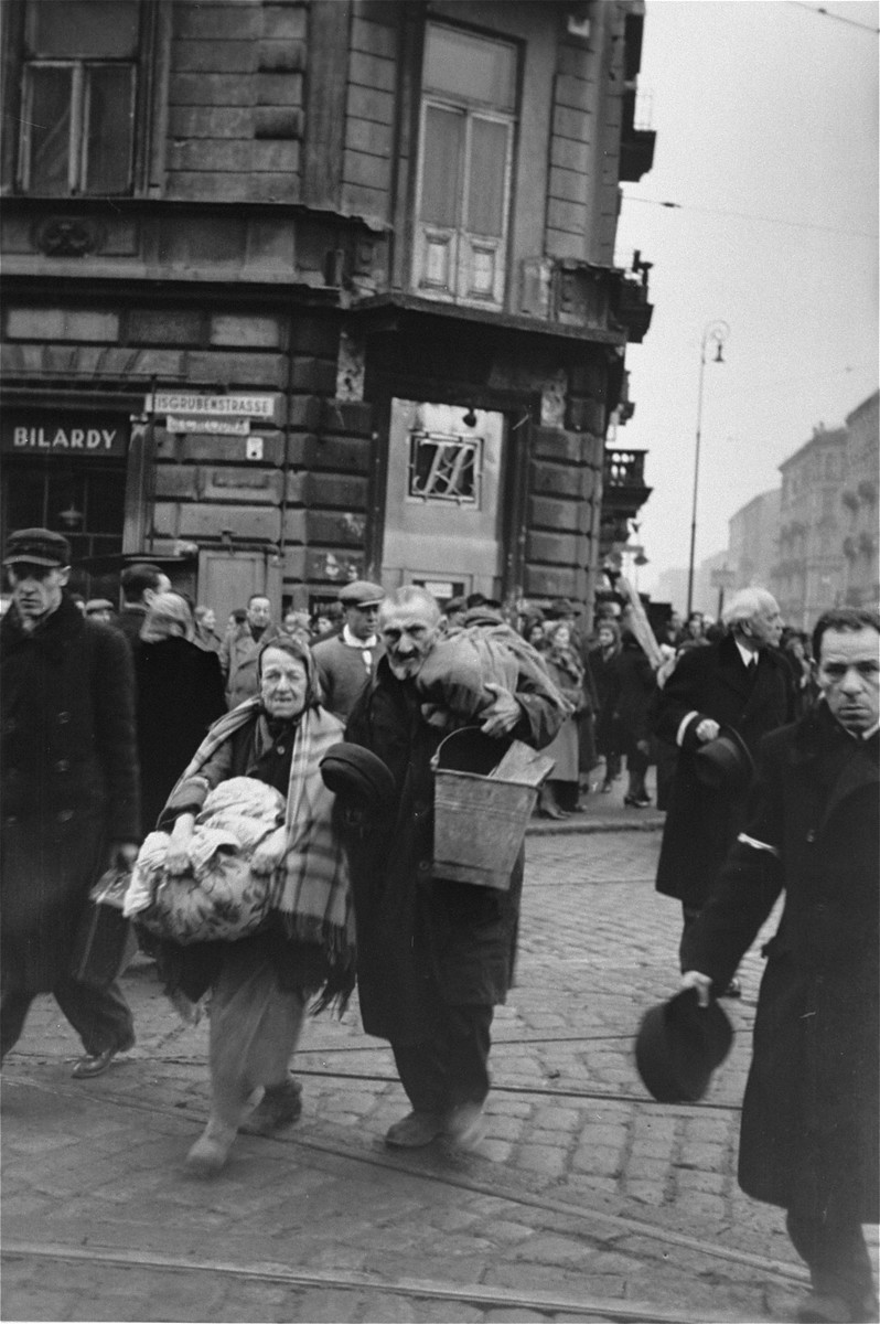 Jewish pedestrians crossing at the intersection of Chlodna and Zelazna Streets in the Warsaw ghetto, doff their hats to the German photographer.