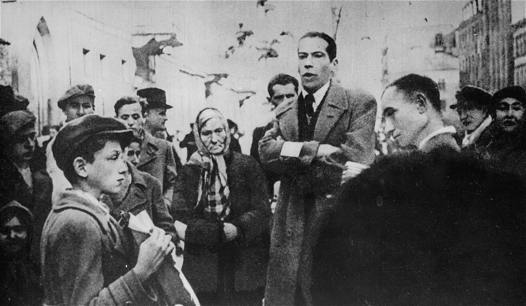 The famous opera singer, Dotlinger, performs on the street in the Warsaw ghetto.