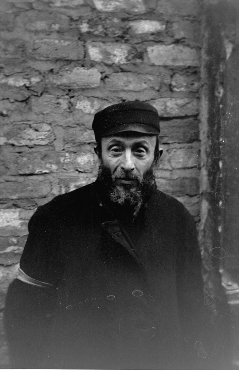 Portrait of a Jewish man standing in front of a brick wall in the Warsaw ghetto.