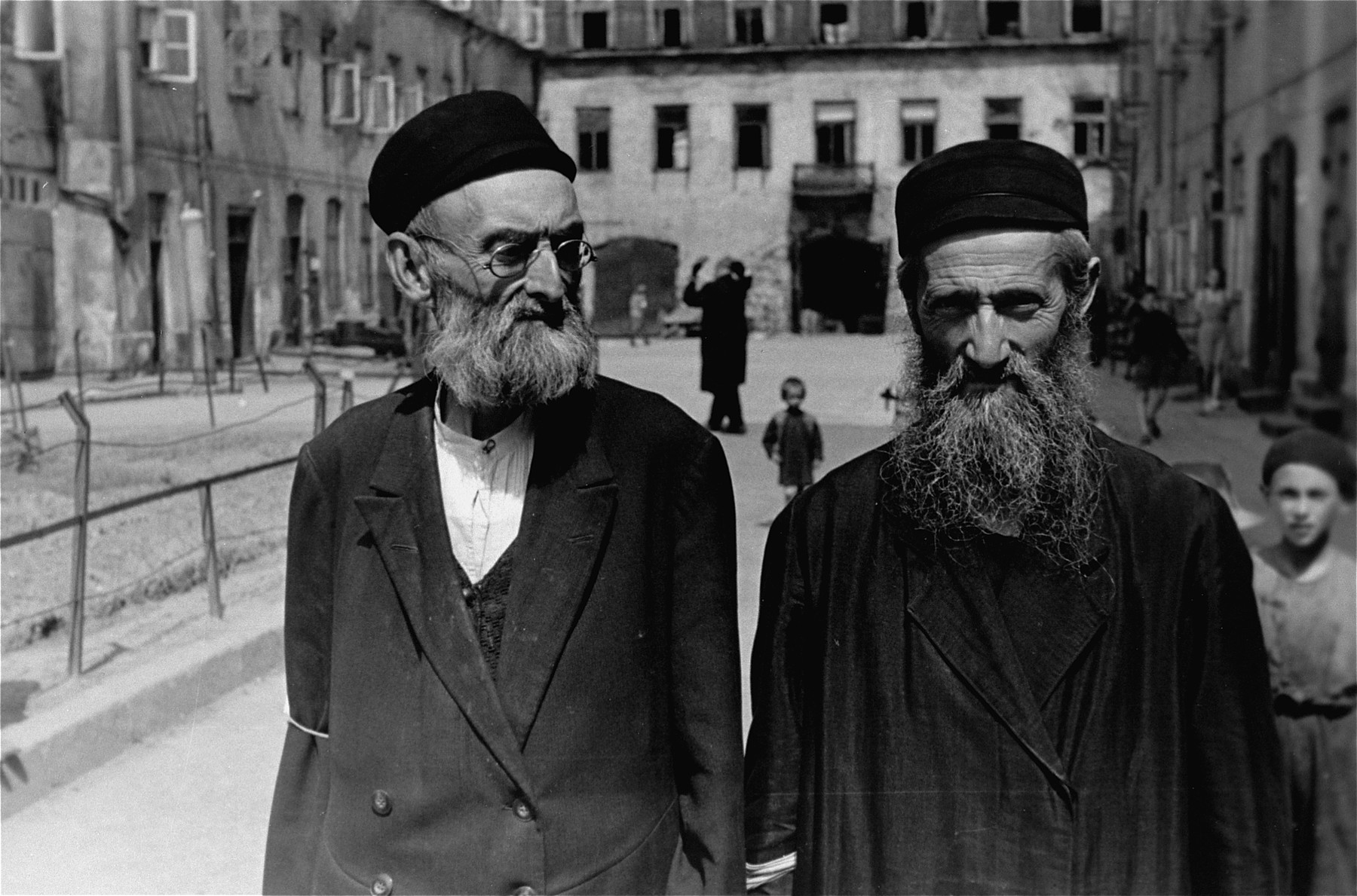 Two bearded, religious Jews walk across a courtyard in the Warsaw ghetto.