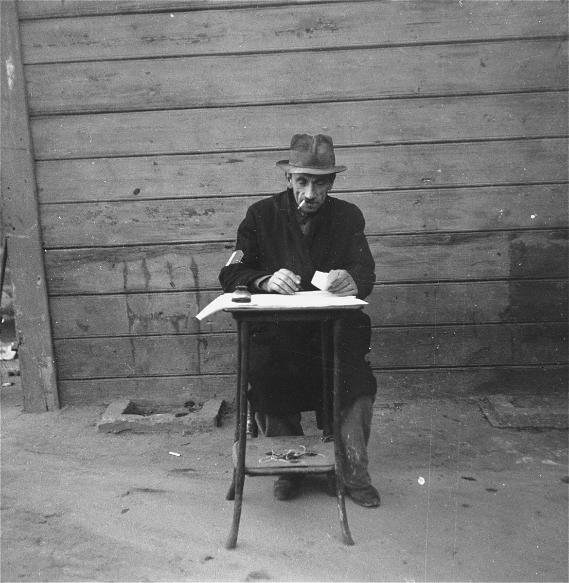 """A man seated at a small table in the Jewish cemetery records in his burial register the number of carts bearing bodies that arrived that day.    Joest's original caption reads: """"This man made an entry in his book of the body carts that arrived in the cemetery.  However, I had the impression that he never once counted the exact number of dead."""""""