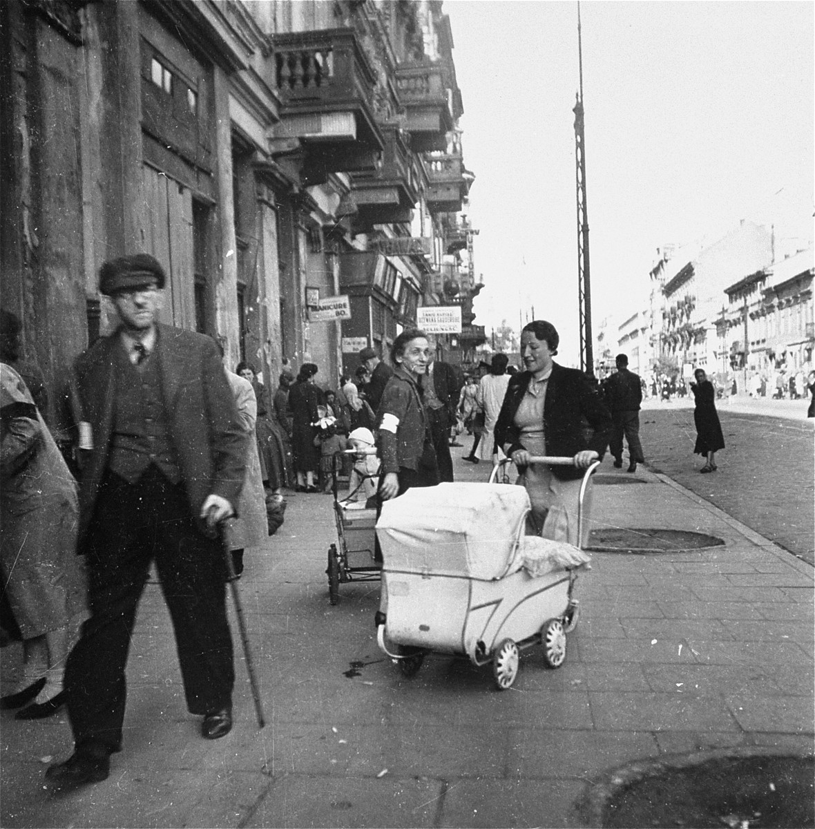 """Two Jewish mothers on Leszno Street in the Warsaw ghetto.    Joest's caption reads: """"It looked like a normal street scene.  Furniture stores, a manicure shop, two women with baby carriages . . . If only the armbands were not visible.  I believe this was the Gerichtsstrasse, which was earlier called Leszno Street."""""""