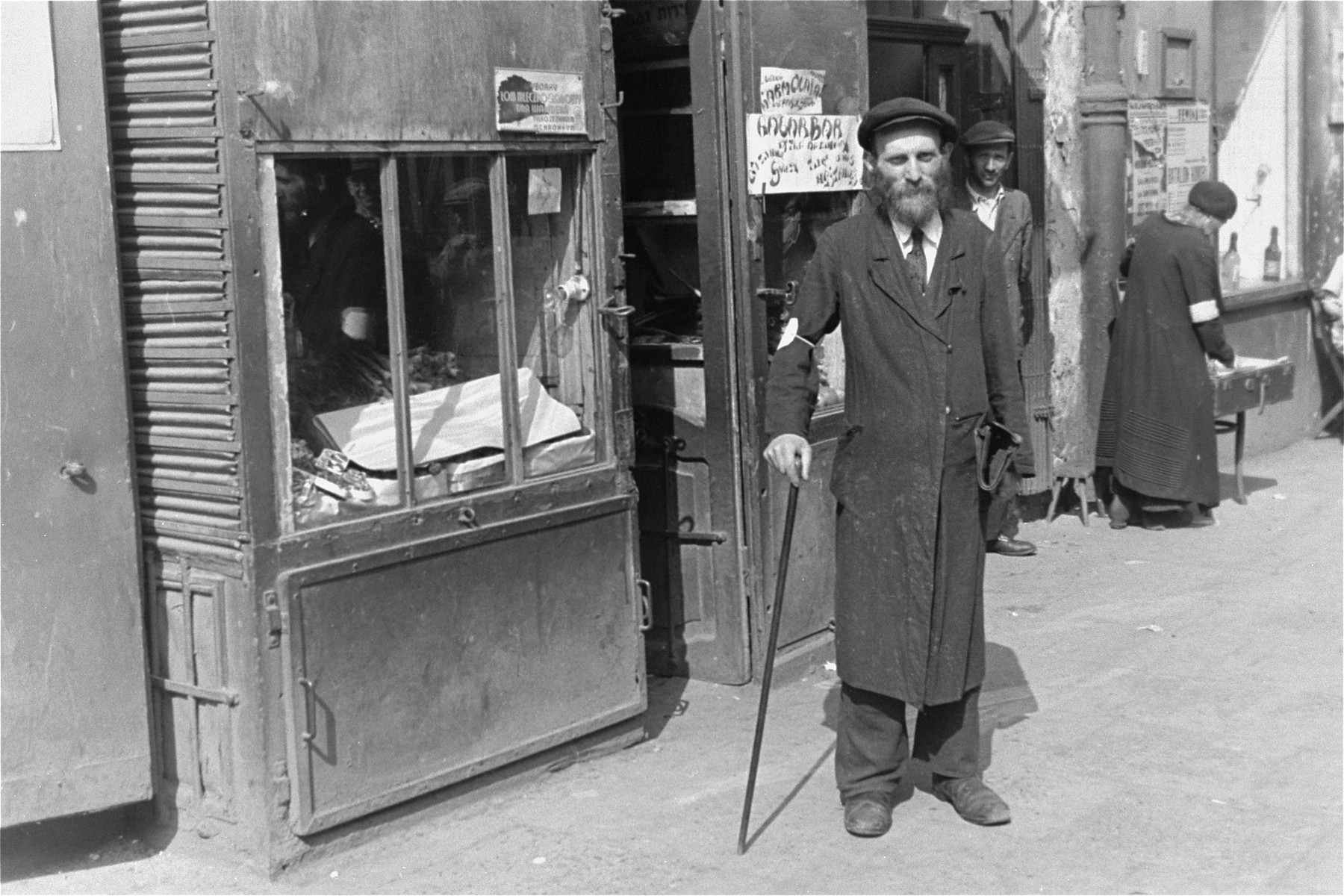 An Jewish man walks along a street in the Warsaw ghetto with a cane.