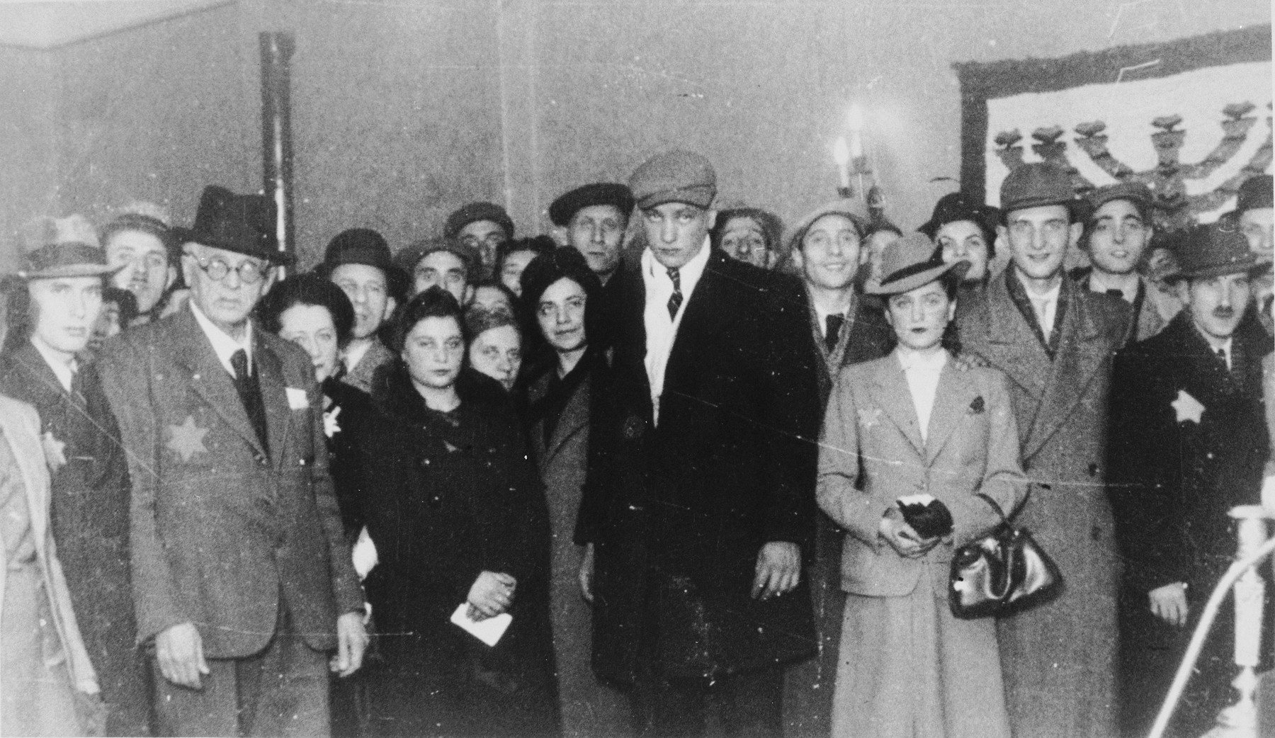 Jewish council chairman Mordechai Chaim Rumkowski, poses with a group of people at a ceremony in the Lodz ghetto.