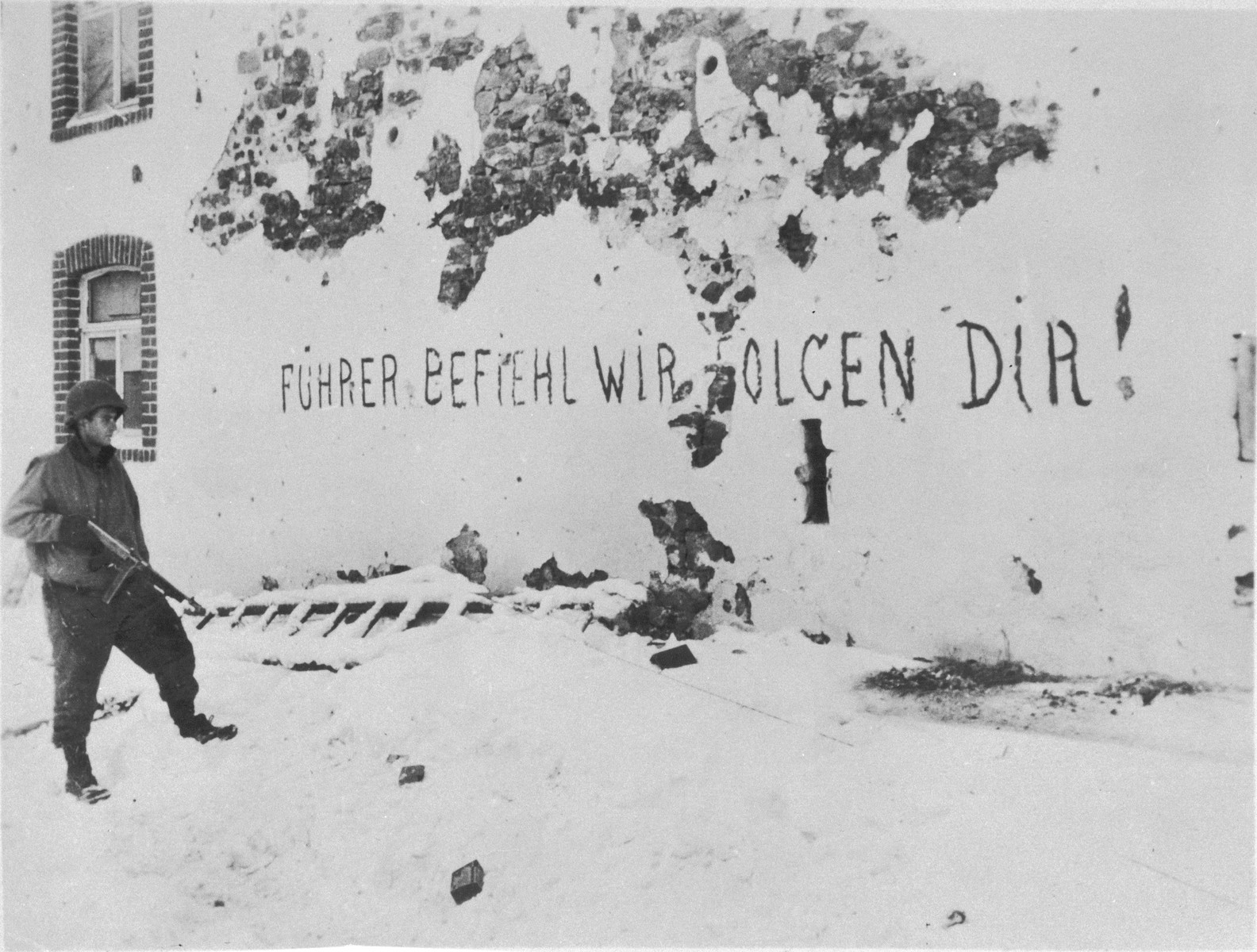 """An American soldier views a German slogan scrawled on the side of a building which reads: """"Fuehrer give the order, we will follow."""""""