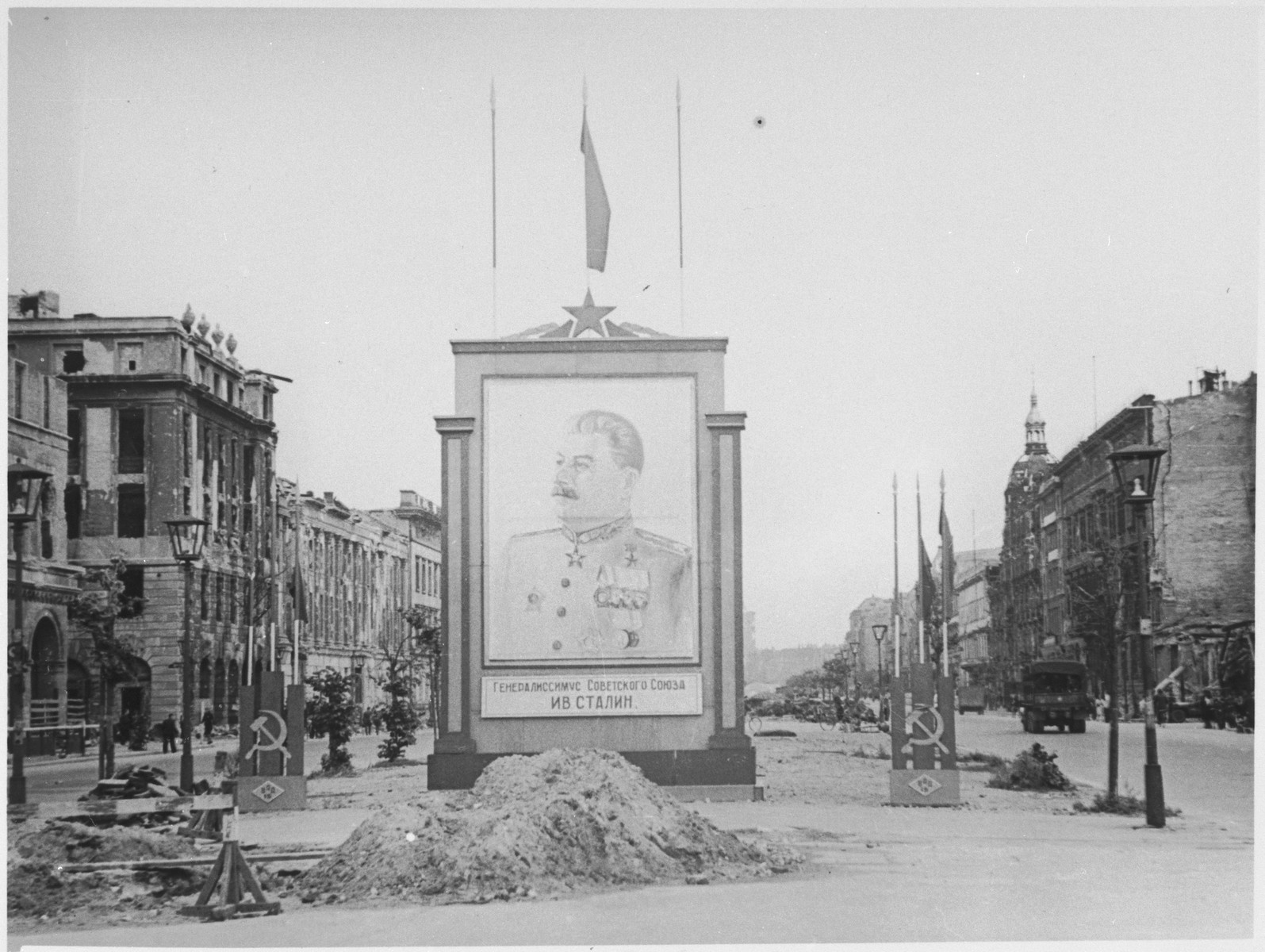 A portrait of Stalin stands in a street in Berlin after the fall of the city.