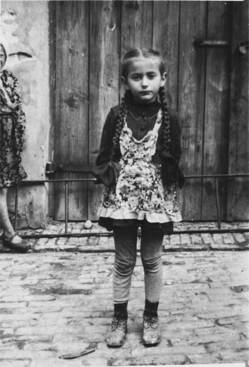Thea Borzuk stands in a Lublin courtyard shortly after her liberation.