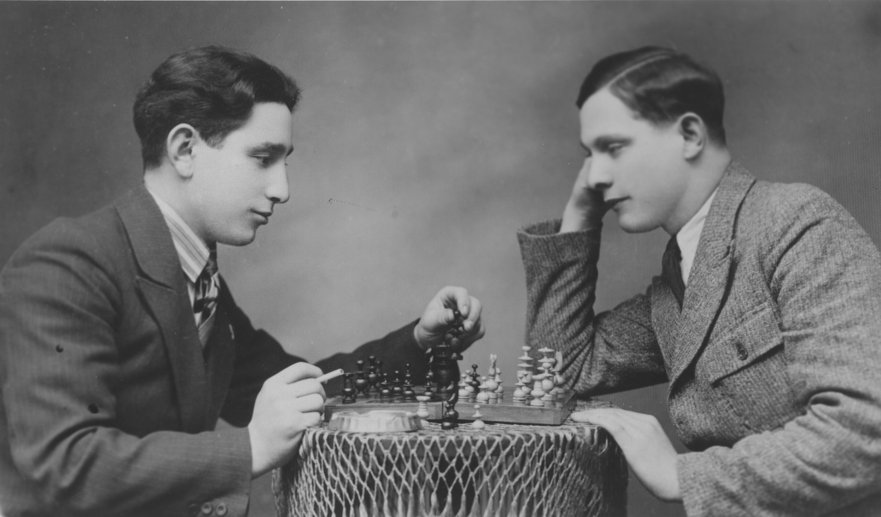 Two Jewish brothers play a game of chess in their home in Tomaszow Lubelski, Poland.  Pictured from left to right are Shmuel (Miles) and Yona Lerman.