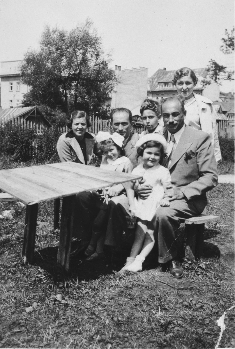 The Kohane family sits by an outdoor table in a garden.  Bernard Kohane is seated second from the left holding Annetta on his lap.  Behind him is Karol and standing in the back is Renia.  Bernard's brother, Karl, is seated on the right.