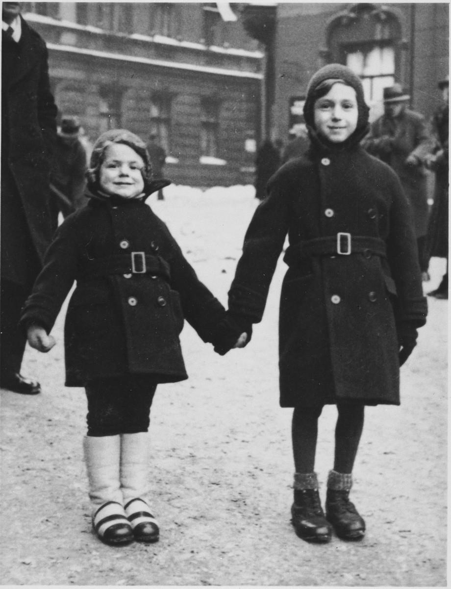 Kazik and Annetta Kohane, dressed in winter coats, stand on the street outside their home in Katowice.