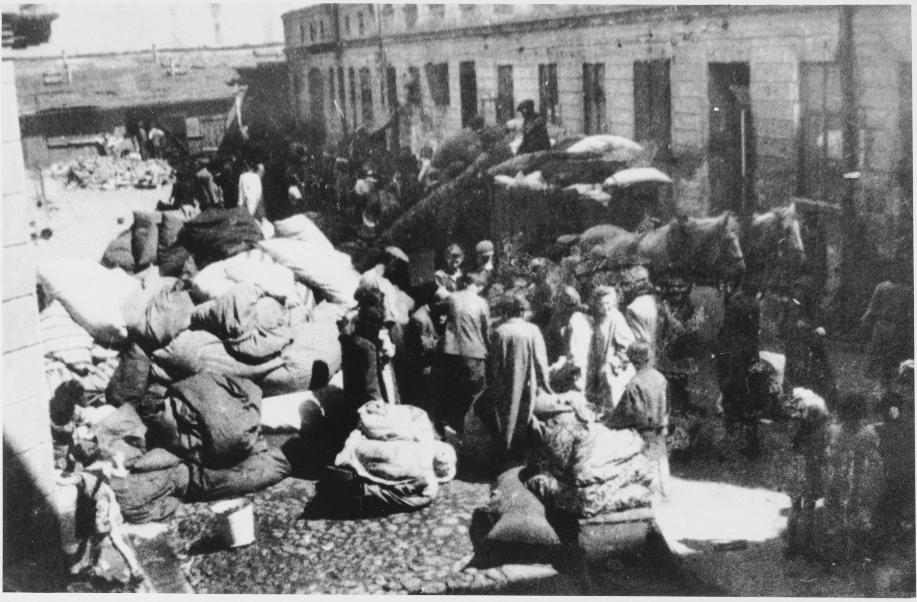 Jews stand among piles of household possessions while waiting to move into the Lodz ghetto.
