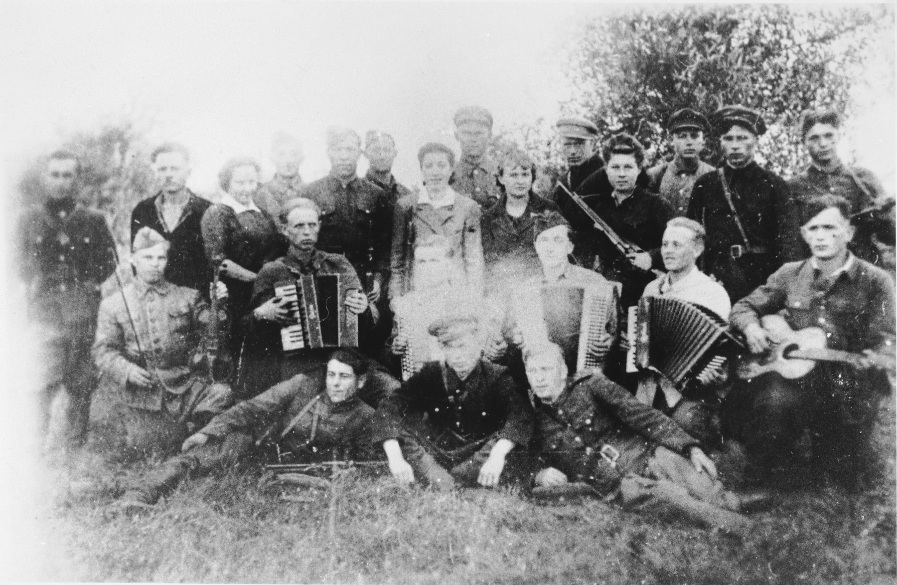 Group portrait of a Jewish partisan musical troupe in the Narocz Forest in Belorussia.    Among those pictured are Hana Posner (standing in the back row, seventh from the left), her father, Mordechai Posner (fourth from the left) and Yechiel Burgin (sixth from the left).