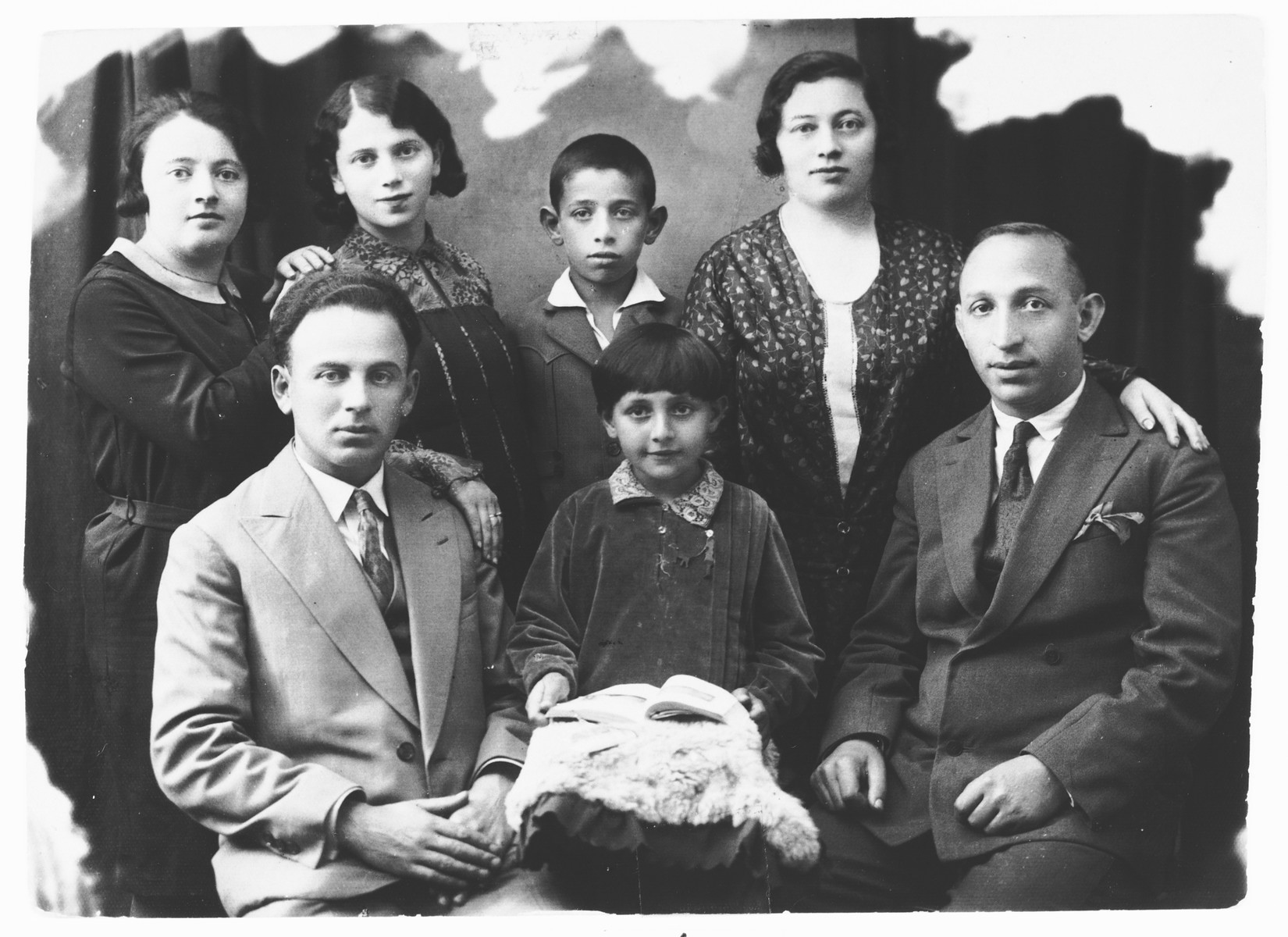 Prewar studio portrait of the Weissman family.  Those pictured include Rivka Weissman (top row, second from the left) and her sisters, Pauline Weissman Smoelevich (top row, far left) and Gnedel Pomerancz (top row right).  Gnedel's daughter Rushka is seated in the front row, center next to her father.  Of those pictured, only Rivka and Pauline survived.