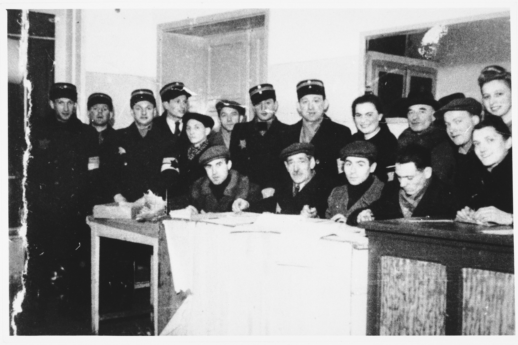 Members of the Jewish police pose with administrators in an office in the Lodz ghetto.