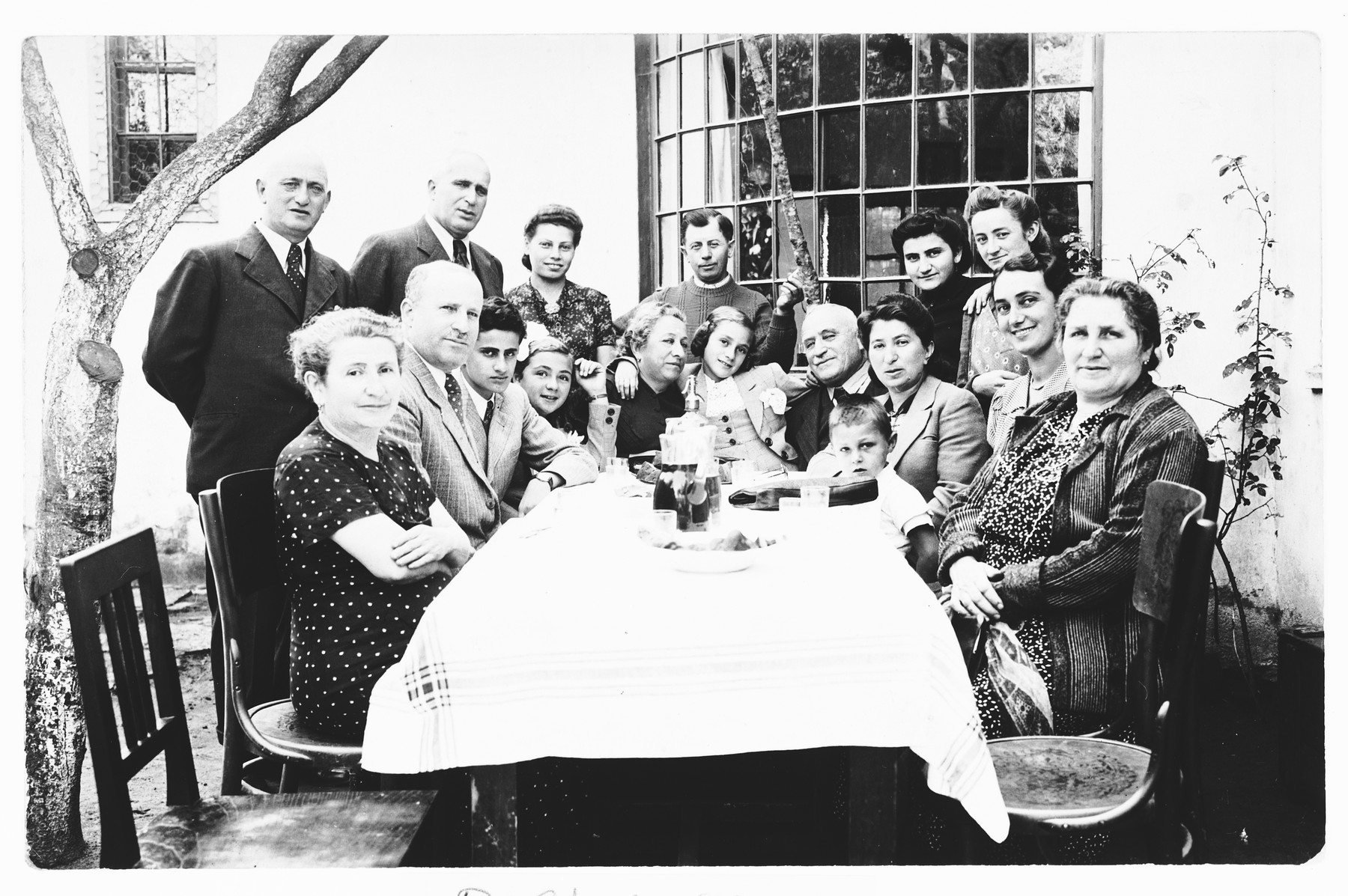 The extended Krasso and Spitzer families pose outside around a table at a family gathering shortly before the start of the war.  Among those pictured are Miriam Spitzer (fourth from the left), her mother Ilonka Spitzer (second from the right) and sister Leah (center next to her grandparents).