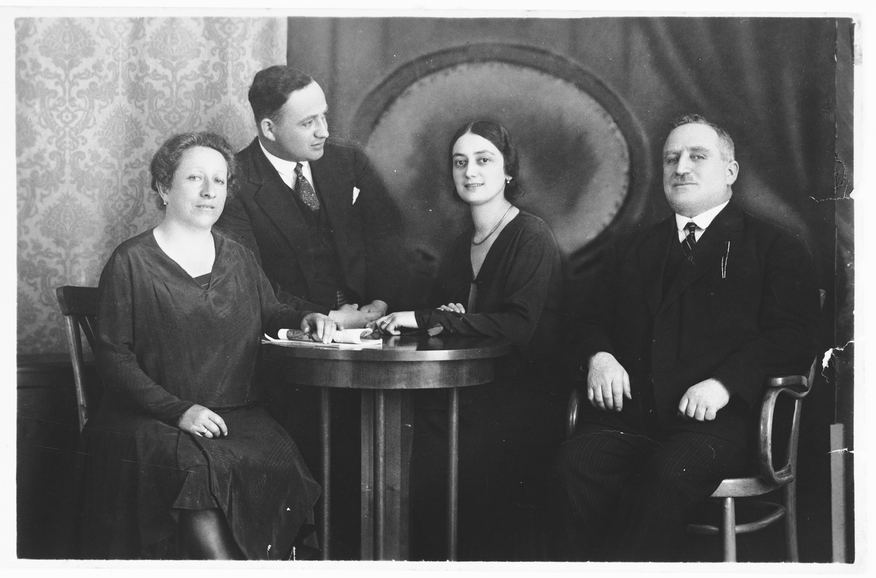 Studio portrait of a Jewish family taken on the occasion of the engagement of their children.  Pictured are Marko Spitzer and Ilonka Krasso (center) with Marko's parents.
