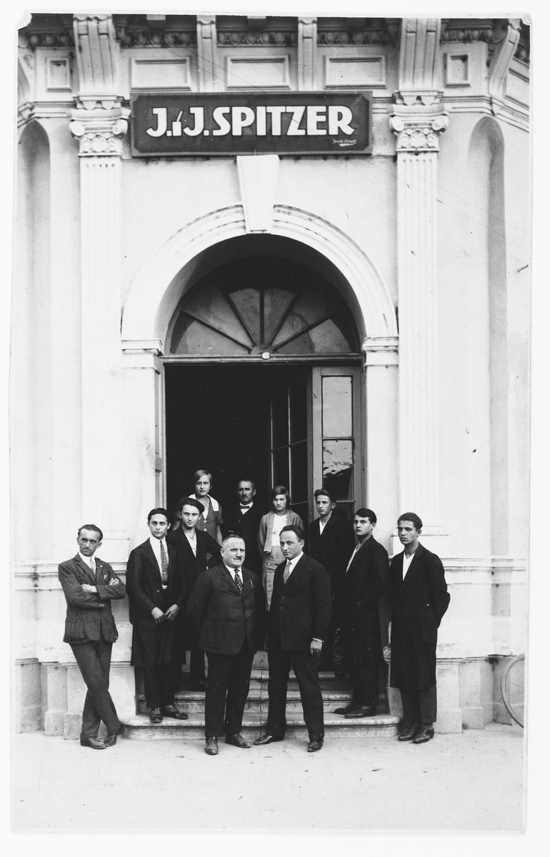 Employees of the J.J. Spitzer textile importing firm pose at the entrance to their building in Osijek, Croatia.    Marko Spitzer and his father stand in the center.