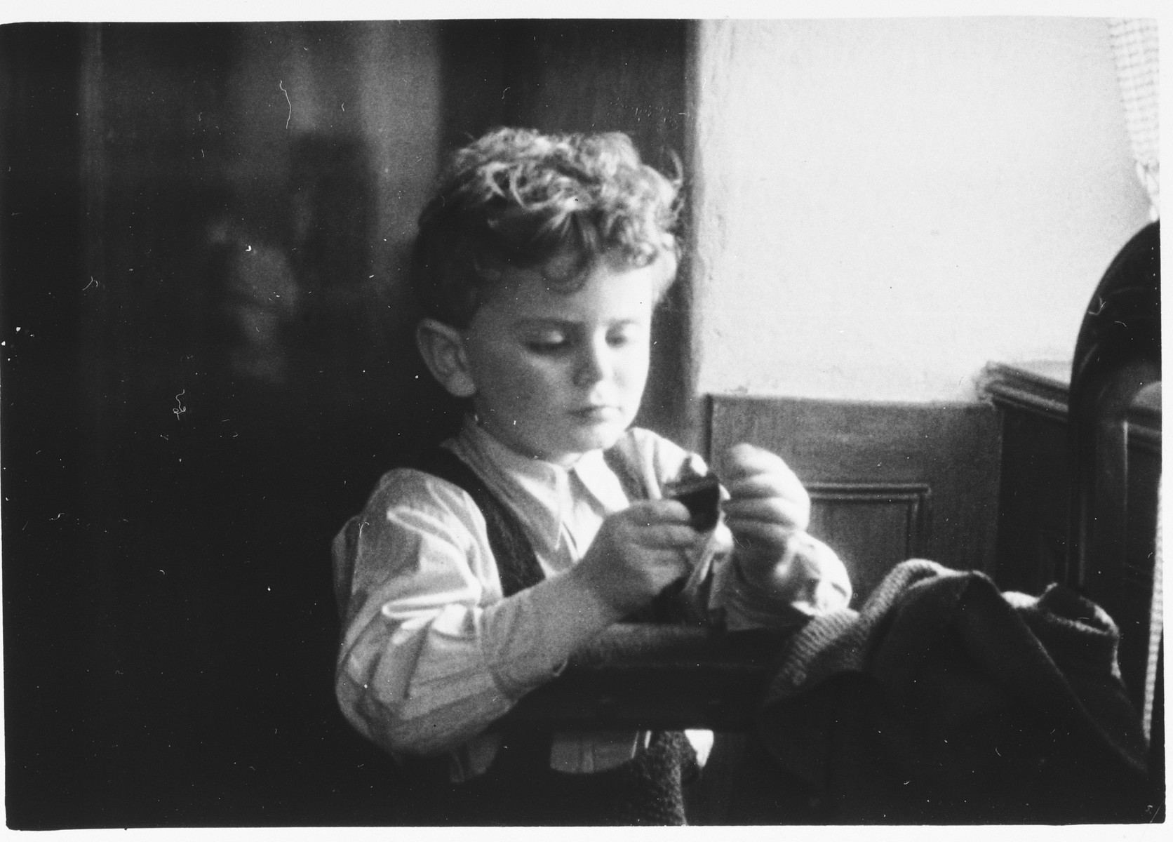Portrait of Petr Polak playing with a puzzle taken shortly before he was deported to Theresienstadt where he perished.