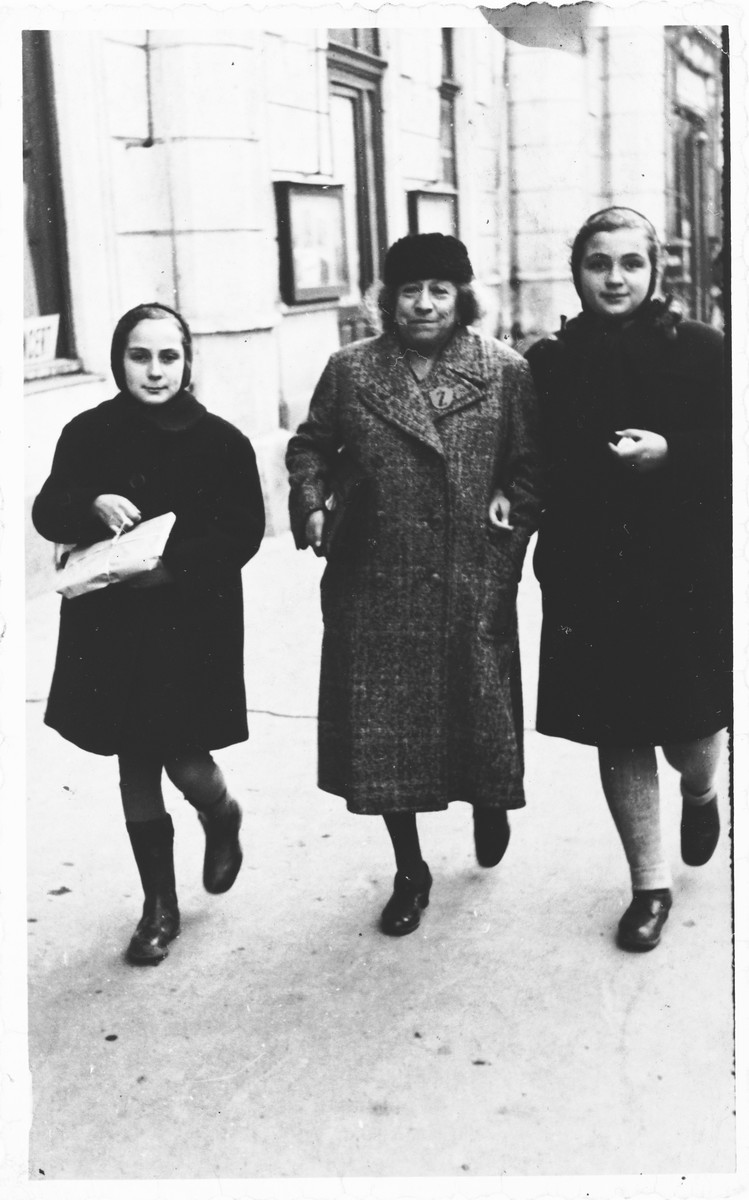 Two Jewish sisters walk along a street in Osijek, Croatia with their grandmother, who is wearing a Jewish badge.  Pictured are Miriam Spitzer (right) and Leah Spitzer (left).
