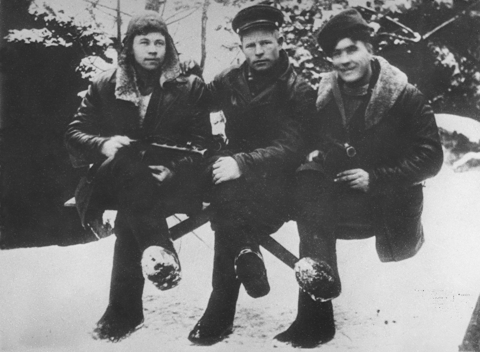 Three intelligence scouts of the Shish detachment of the Molotov partisan brigade pose outside in the snow.