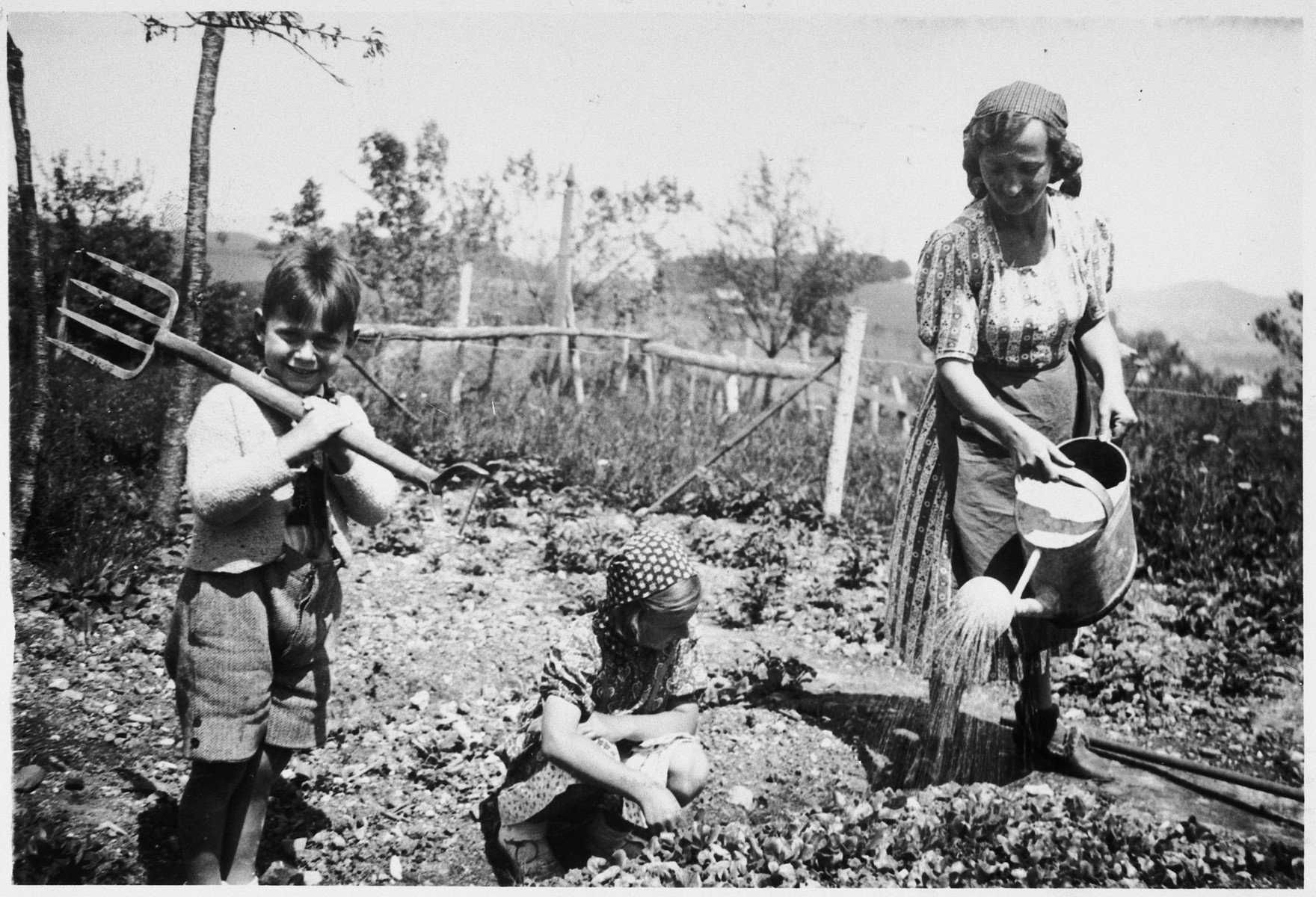 Jetti works in her garden assisted by her children Gerhard and Inge.