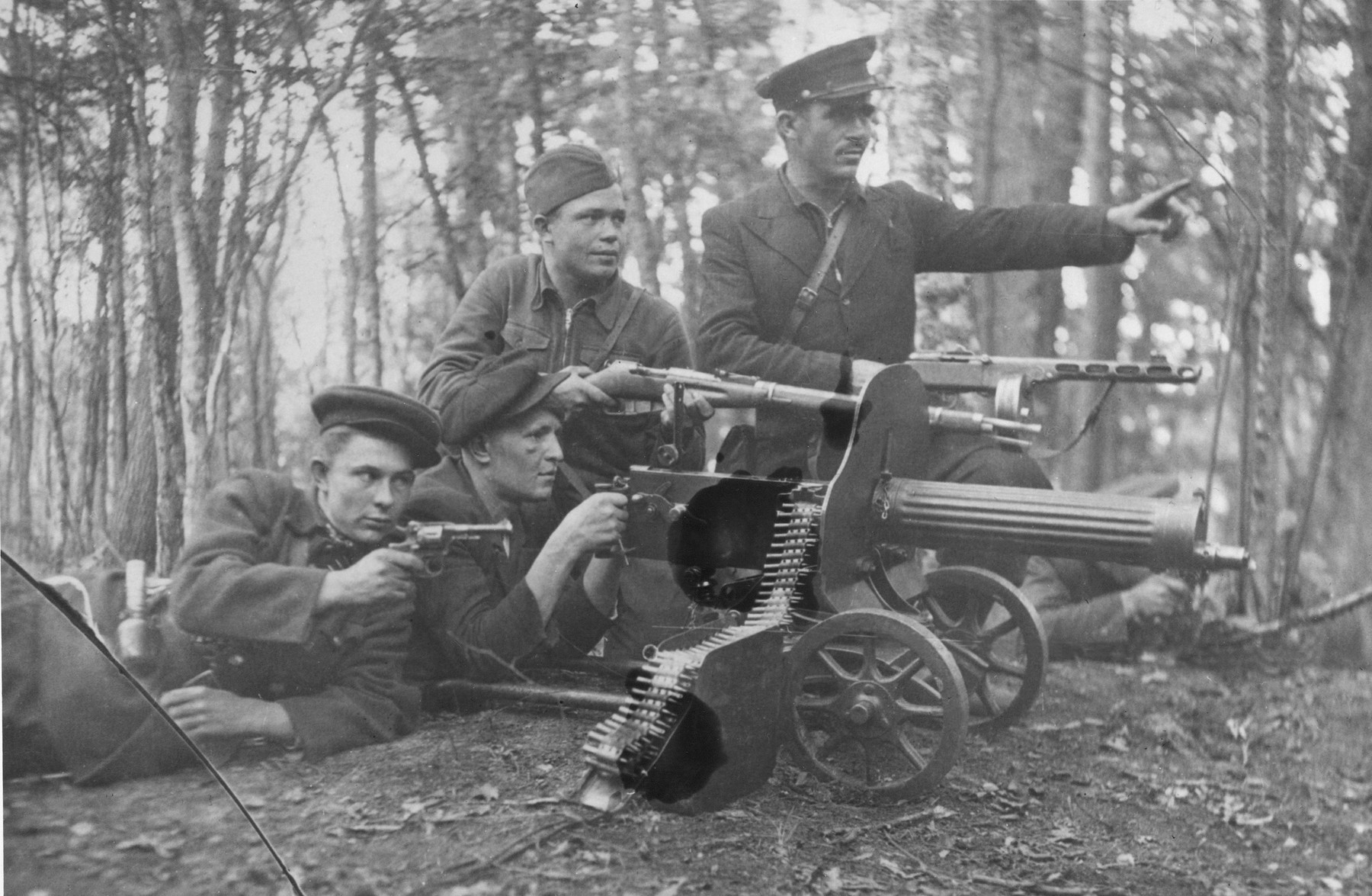 Members of the Shish detachment of the Molotov partisan brigade pose in the forest with their weapons.