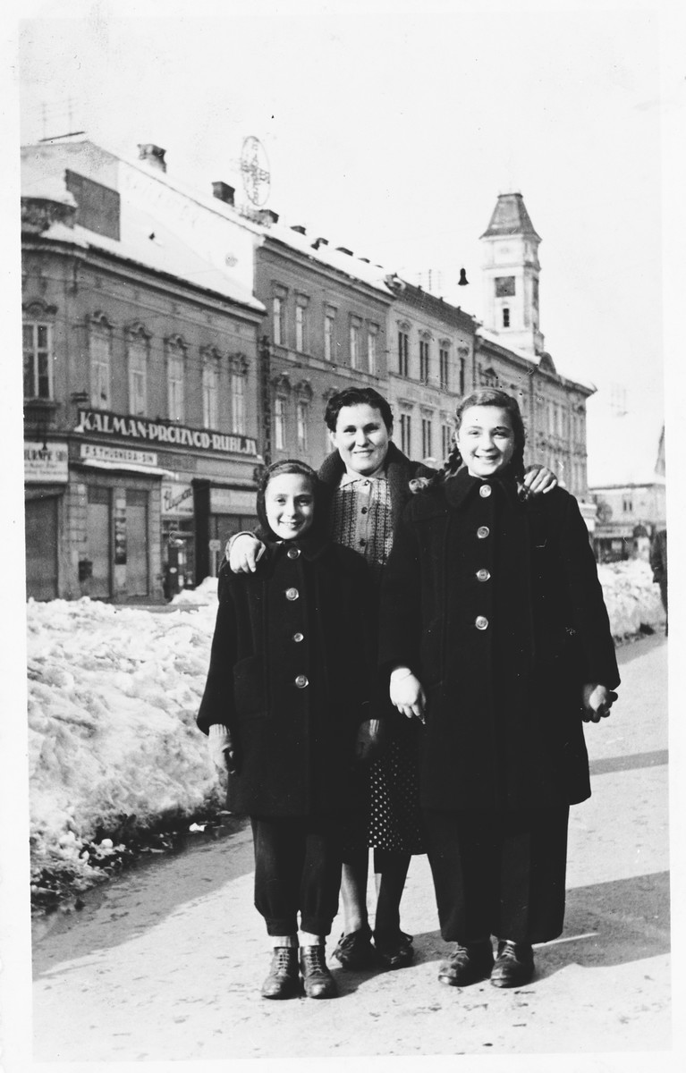 Two Jewish sisters pose with their nanny on a street in Osijek, Croatia.  Pictured in front are Miriam Spitzer (right) and Leah Spitzer (left).