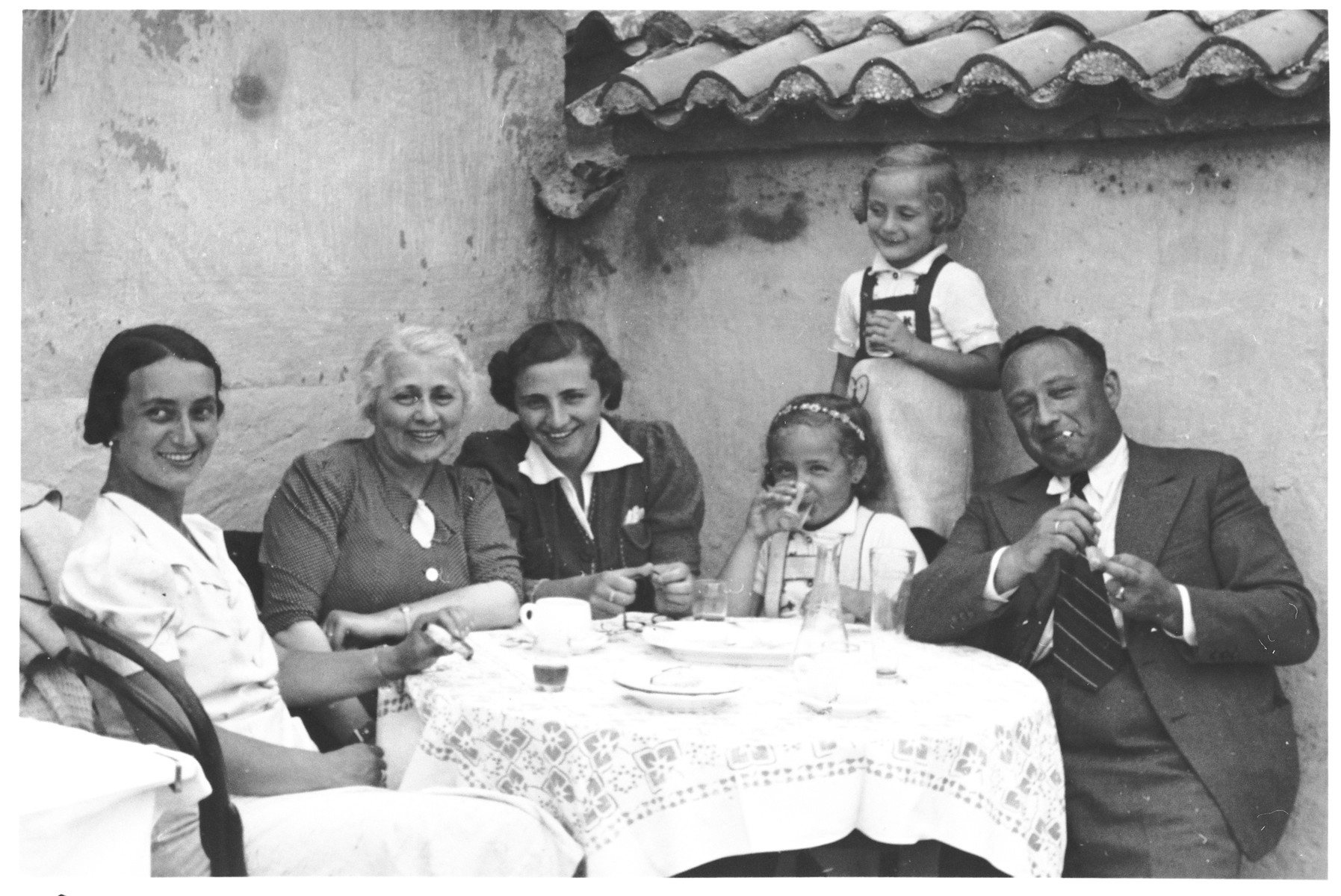 Members of the Spitzer family sit outside around a table.