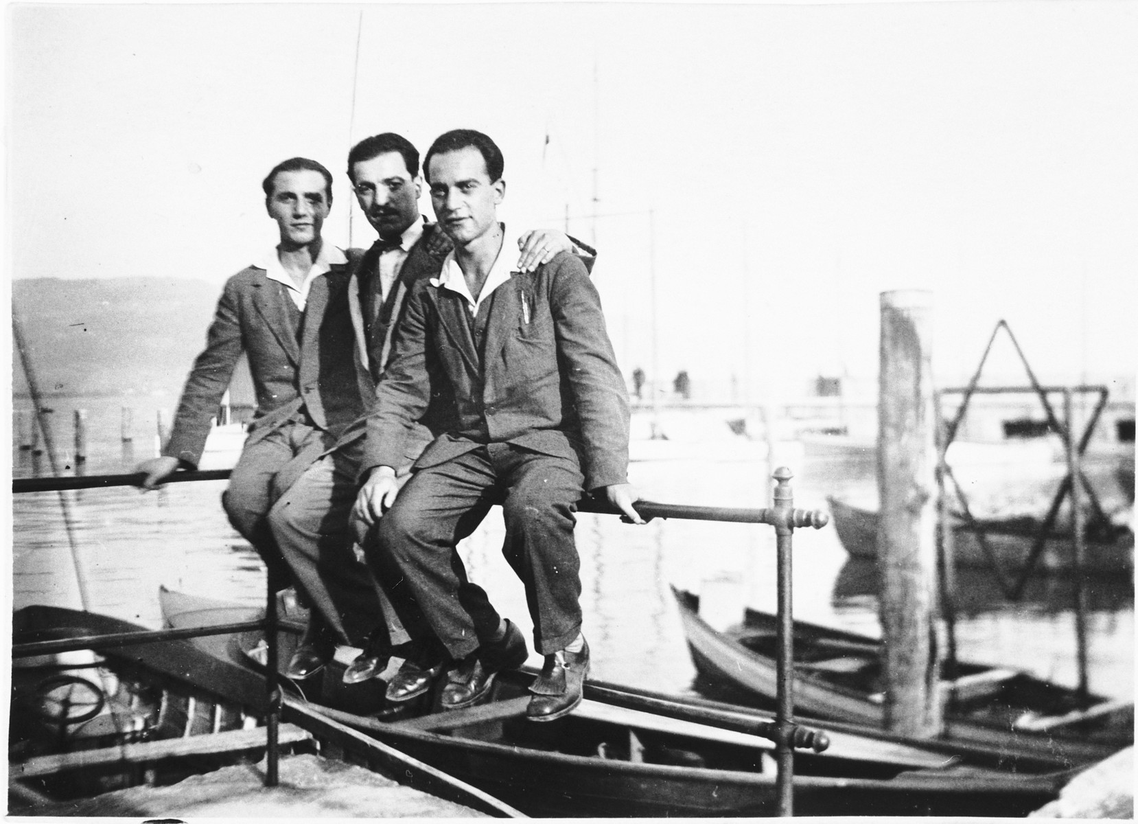 Sigmund Lewitzky (right) and his brothers sit on the railing of a dock.