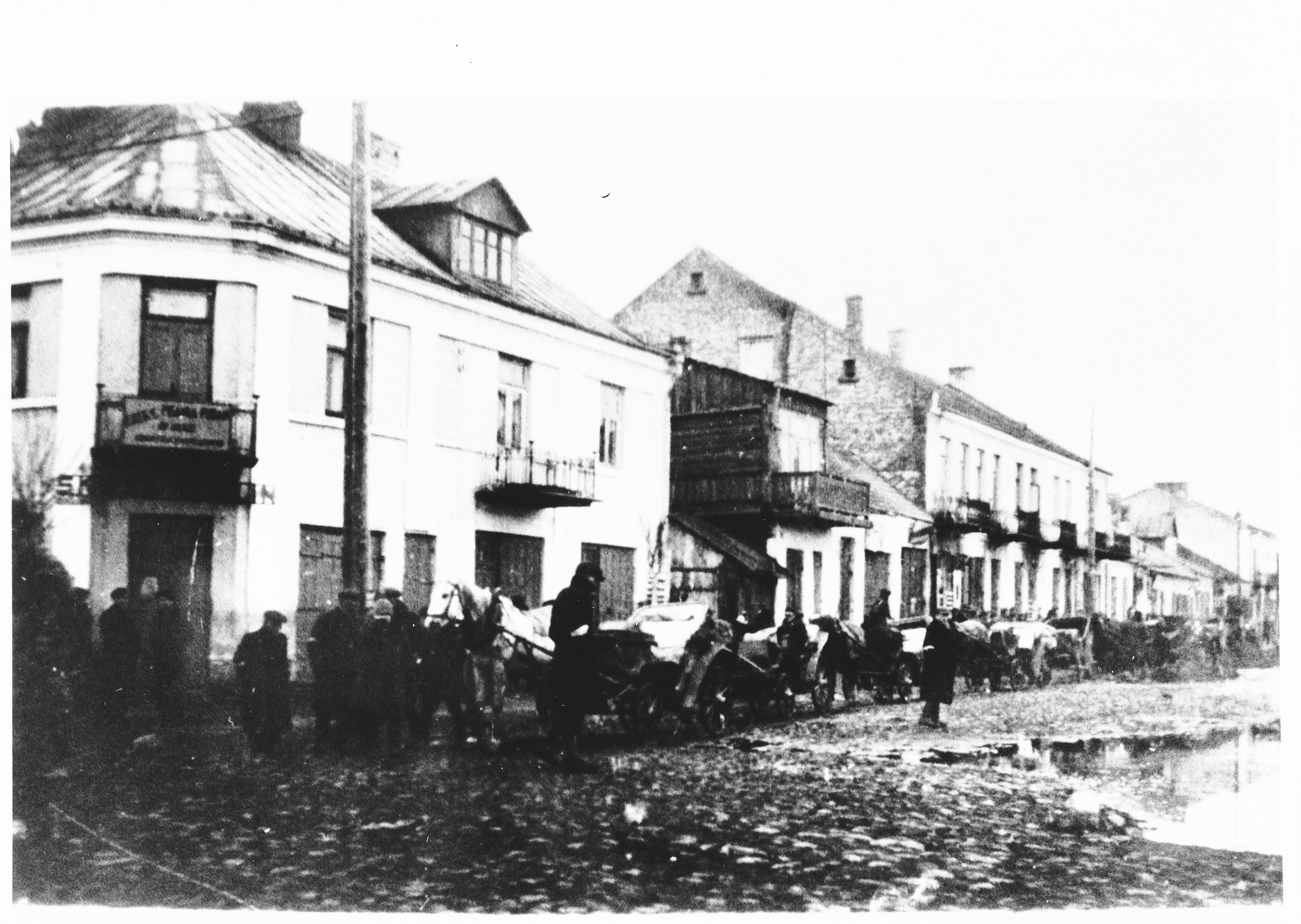 Horse and wagons line the street of an unidentified ghetto.