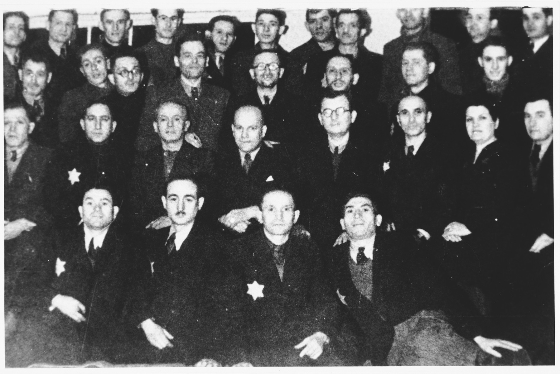 Group portrait of Jewish men in an unidentified ghetto wearing Jewish stars.