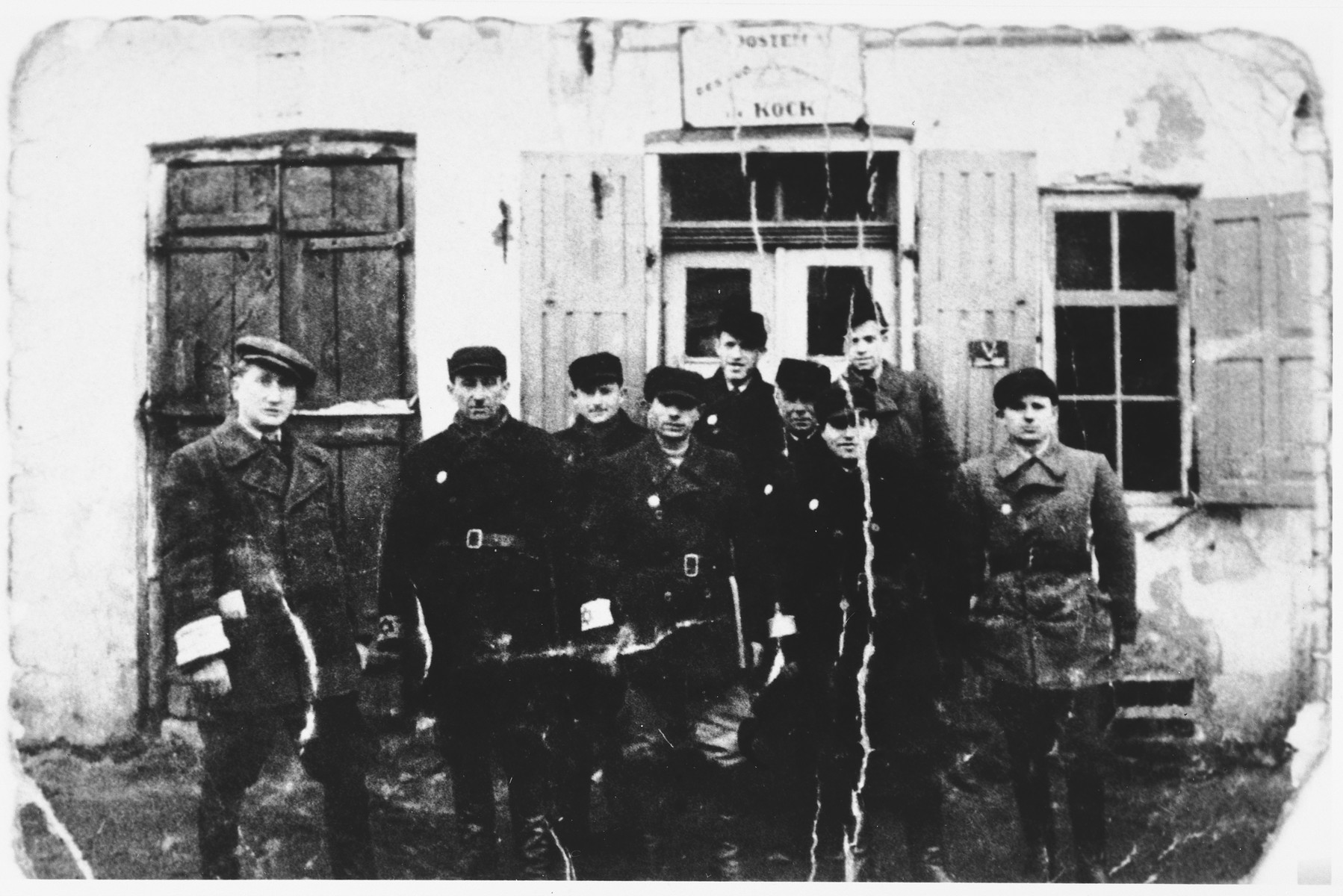 Jewish workmen wearing armbands stand outside the Krock building in an unidentified ghetto.