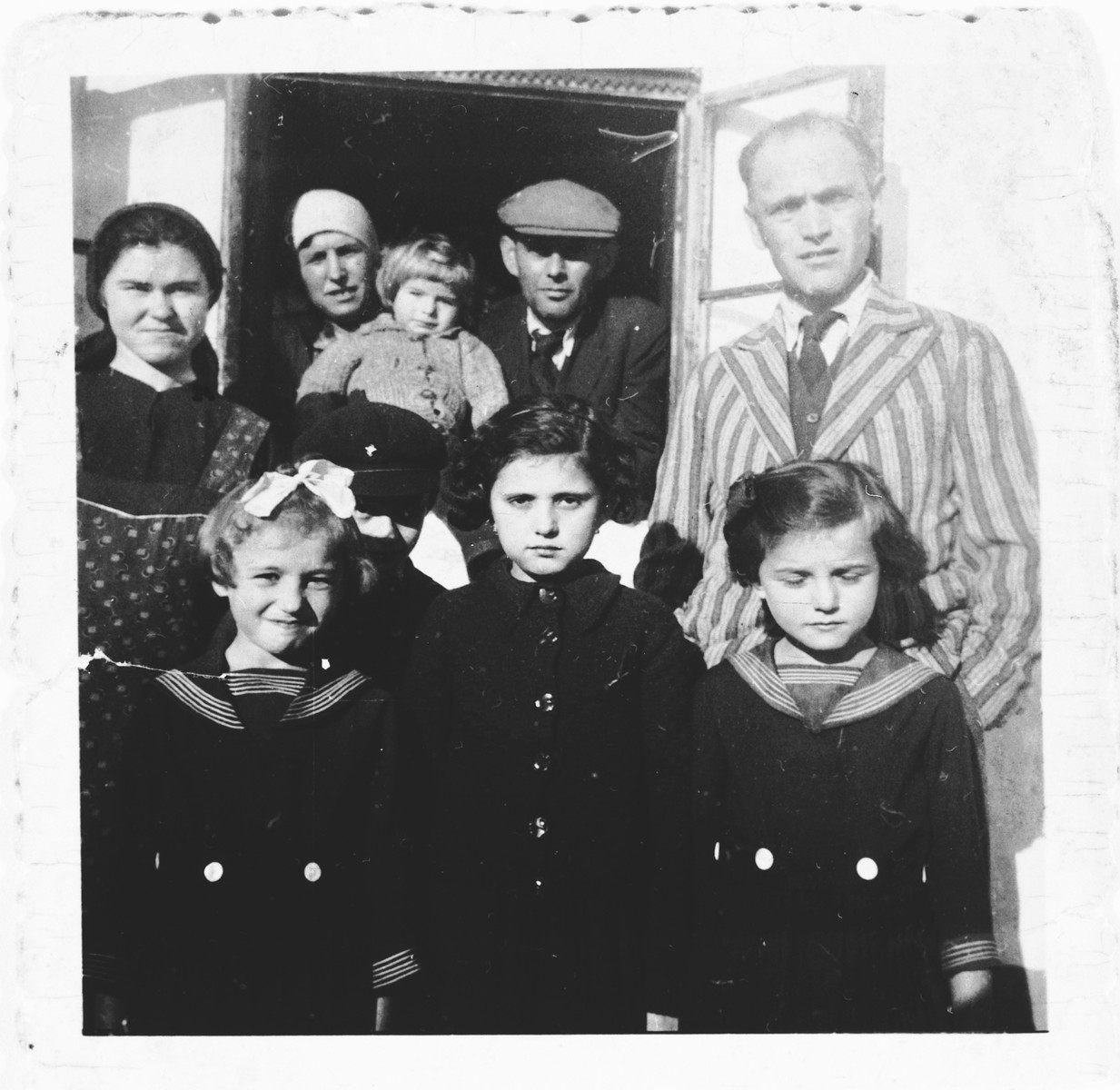 Group portrait of members of a Jewish family outside their home in Bilki.  Pictured in the front row from left to right are: Violet, Magdalena and Hana Mermelstein.  In the top row are: unknown, Bella, Edward, Ludwig and Meyer Mermelstein.