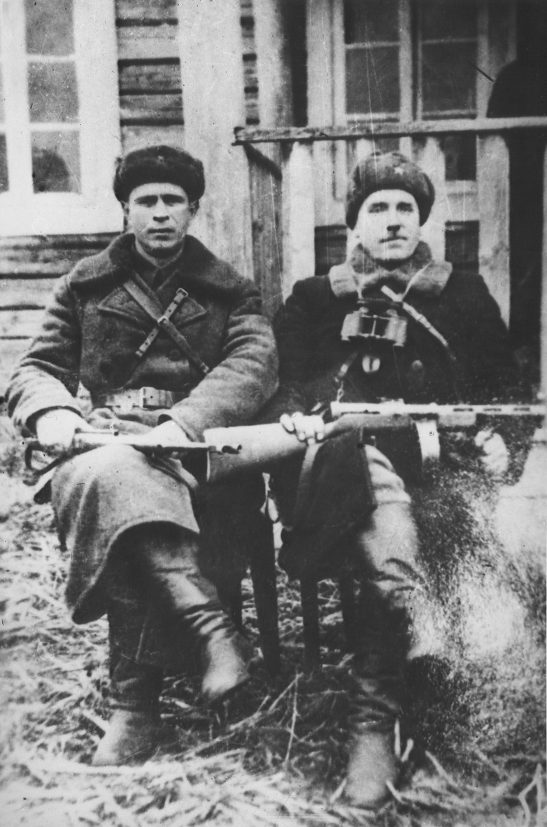 Two commissars of the Molotov partisan brigade pose outside with their rifles.  Pictured on the left is Vasiliy Timofeevich Merkul, commissar of the 101th Aleksandr Nevskiy partisan brigade.  On the right is Ivan Yevmenovich Zhenov, commissar of the Shish partisan detachment.