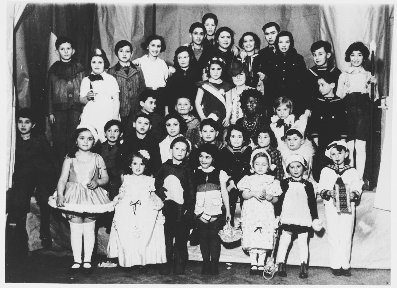 Group portrait of children from the Jewish school in Osijek, Croatia dressed in costume for Purim.   Among those pictured are: Miriam Spitzer (bottom row, left), Leah Spitzer (bottom row, third from the right), Nada Langfelder (bottom row, fourth from the right), Suzy Nadj (second row, fourth from the right), Egon Nadj (profiled, second row from top, on right), and Bella and Ruti Shmukler (top row, center).