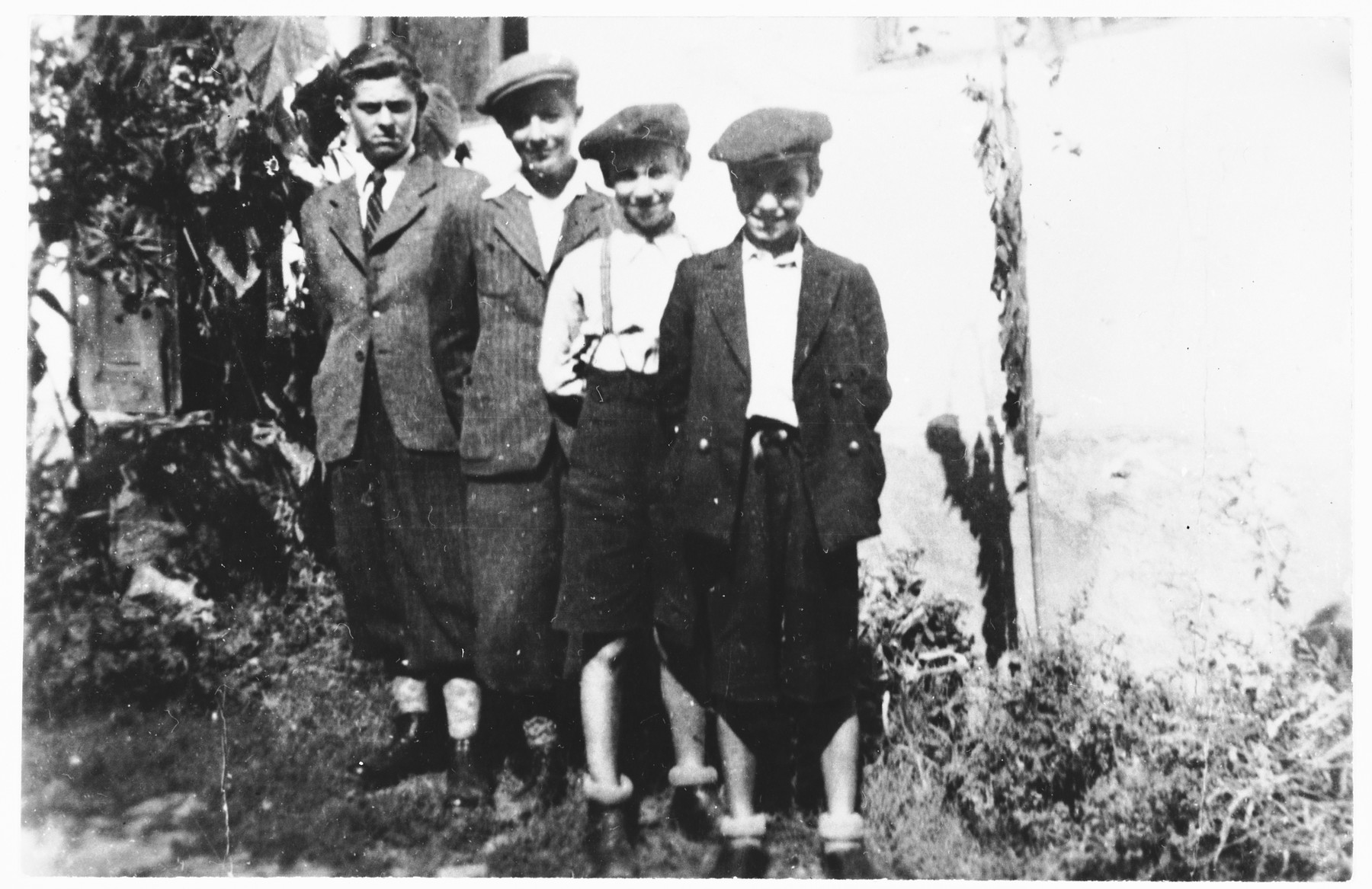 Shlomo, Jakob, Leibush and Dovid Weinberger stand outside their family's house in Mukachevo.