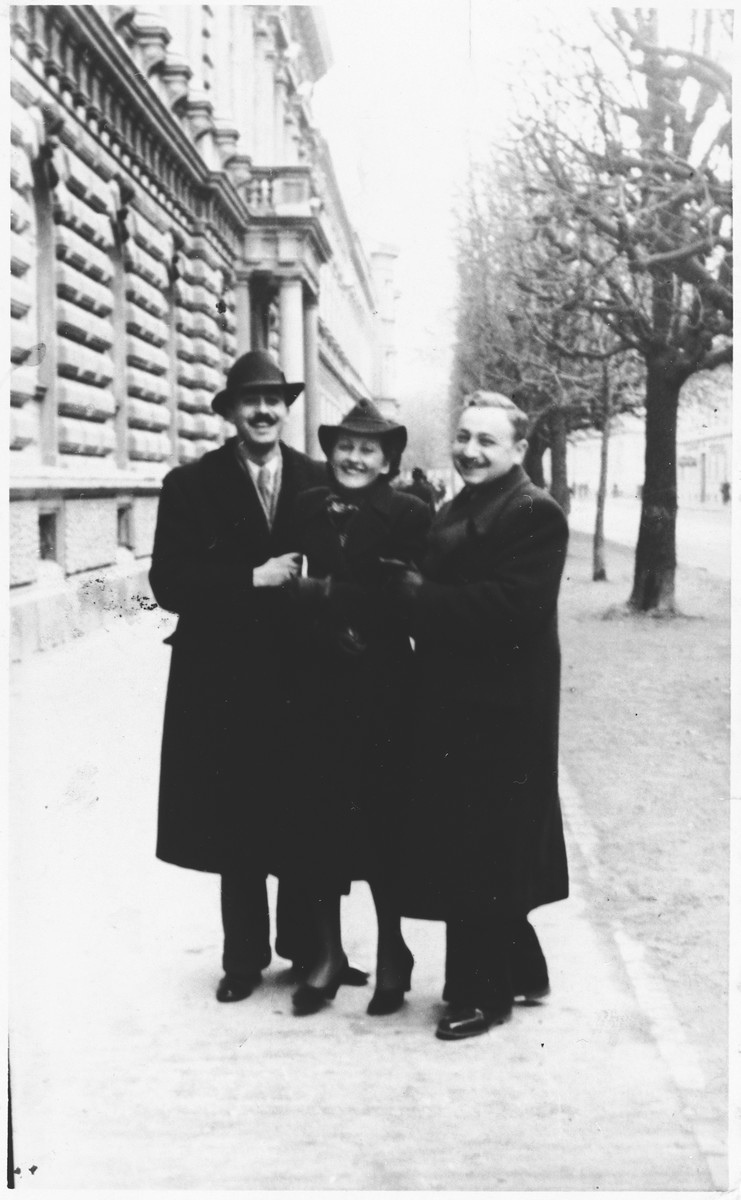 Three young adults pose on a sidewalk in Osijek, Croatia.  Among those pictured is the engineer, Alfred Krasso (left).  He was killed in Jasenovac during the final days of the war.