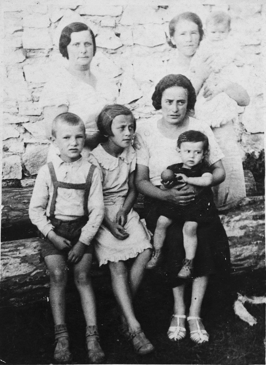 A group of women and children from Olkusz pose together on a log.  Pictured standing (left to right) are Leah Kolin and her neighbor holding her son.  Seated in front (left to right) are a neighbor's son [name unknown], Hela Kolin, and Hela's aunt with her son on her lap.