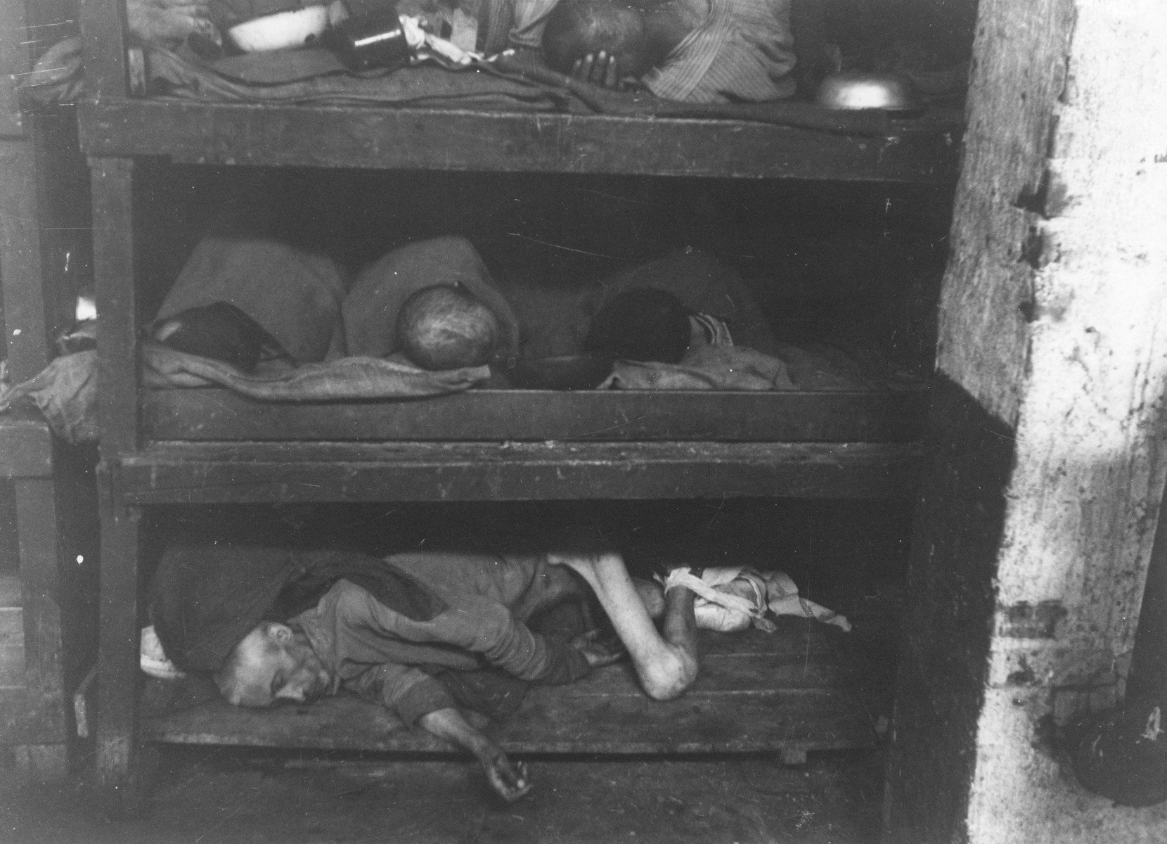"Survivors lie in multi-tiered bunks in the hospital barracks in Buchenwald.   The original caption reads: ""Weimar, Germany...This is typical of a hospital ward in Buchenwald concentration camp, where six prisoners were huddled together on one tier.  The man on the lower tier is dead."""